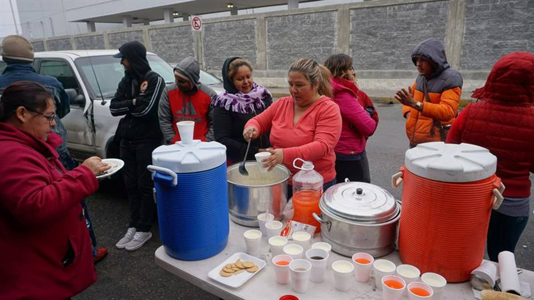 Cuban citizens are fed by locals as they wait in the border line at Nuevo Laredo, Mexico, Jan. 30, 2017.
