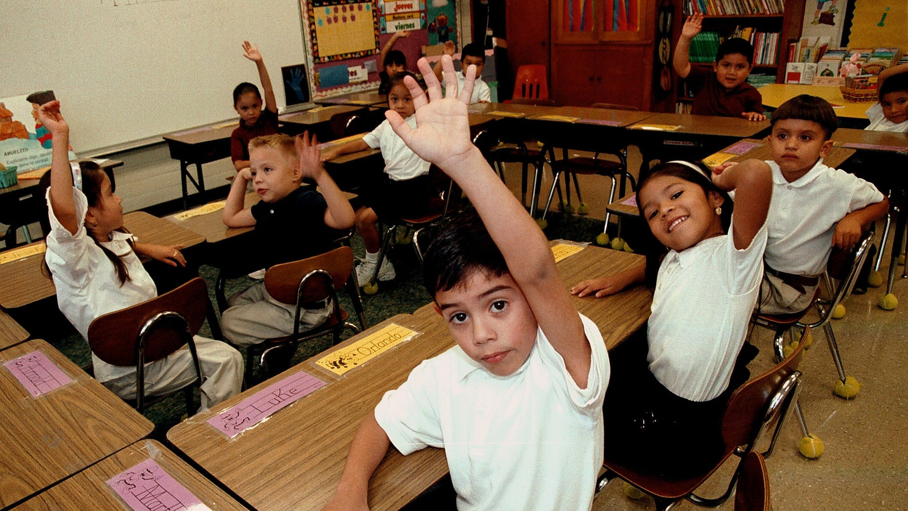 Hispanic students raise their hands to answer a question during a class taught in Spanish at Birdwell Elementary School September 11, 2003 in Tyler, Texas. (Photo by Mario Villafuerte/Getty Images)
