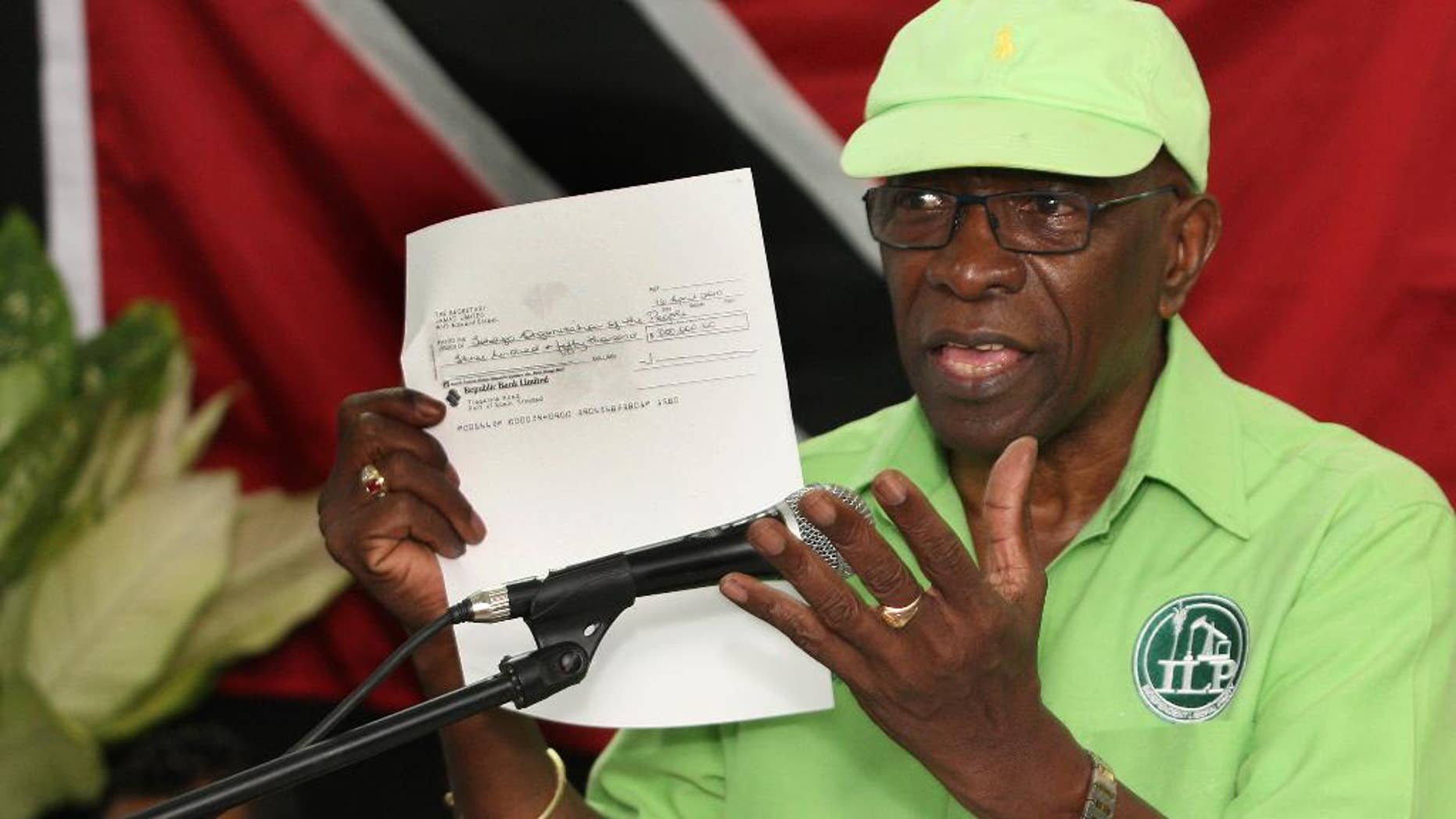 FILE - In this June 3, 2015, file photo, former FIFA vice president Jack Warner hold a copy of a check while he speaks at a political rally in Marabella, Trinidad and Tobago. Trinidad and Tobago's attorney general has signed documents on Monday, Sept. 21, 2015, that pave the way for U.S. extradition proceedings against Warner. The former FIFA vice president is resisting extradition on U.S. charges of racketeering, wire fraud and money laundering in the FIFA corruption case. (Photo/Anthony Harris, File)