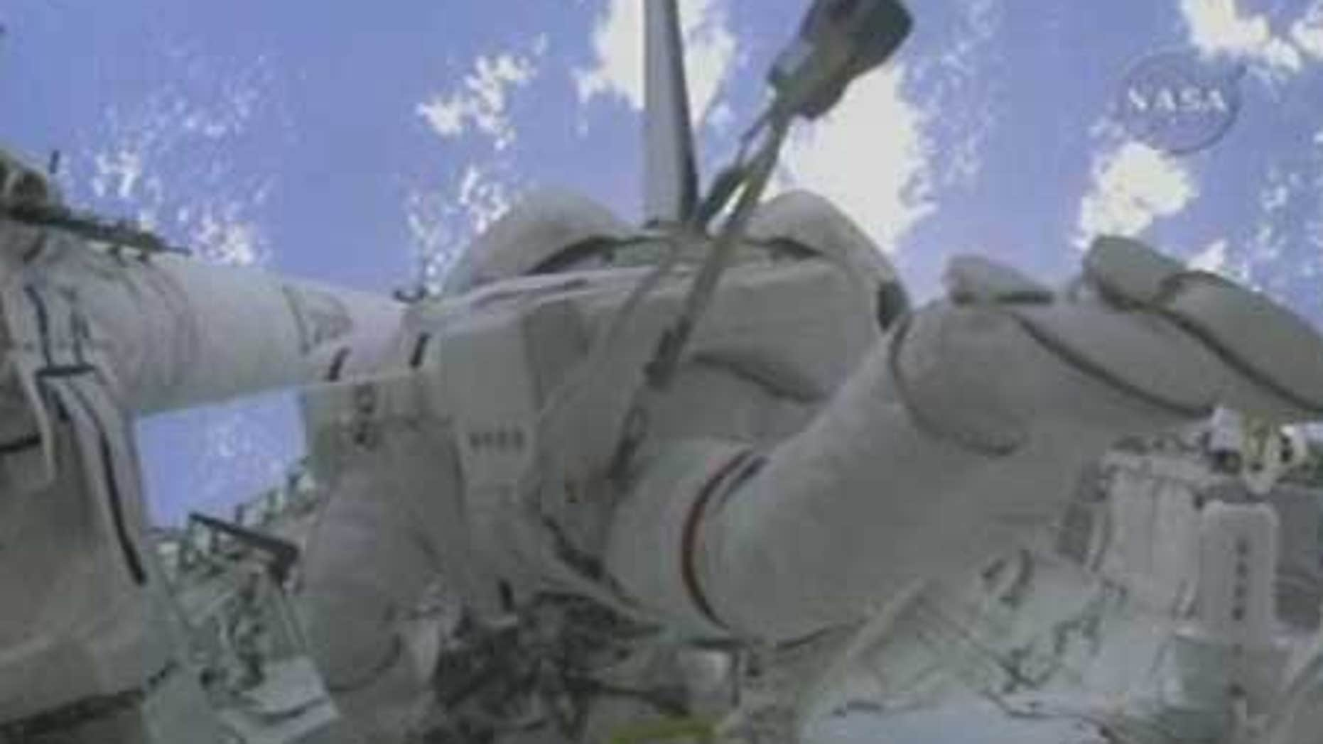 Spacewalkers Mike Foreman and Bobby Satcher at work outside the International Space Station