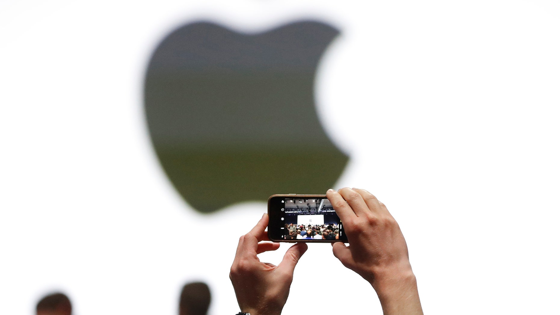 An audience member takes a photo of the Apple logo before the start of the company's annual developer conference in San Jose, California, U.S. June 5, 2017.