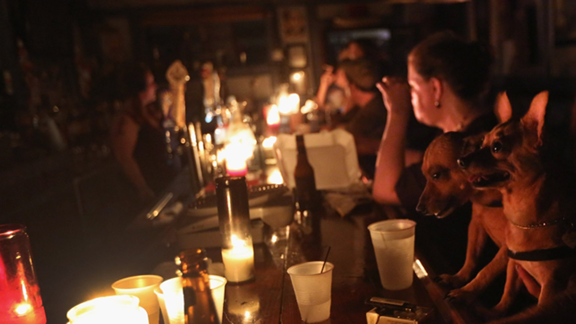 NEW ORLEANS, LA - AUGUST 31:  Local residents drink by candle light at JJ's bar during the continued blackout on August 31, 2012 in the Bywater neighborhood of New Orleans, Louisiana. The area was still without electricity three days after Hurricane Isaac knocked out power to hundreds of thousands of people.  (Photo by John Moore/Getty Images)