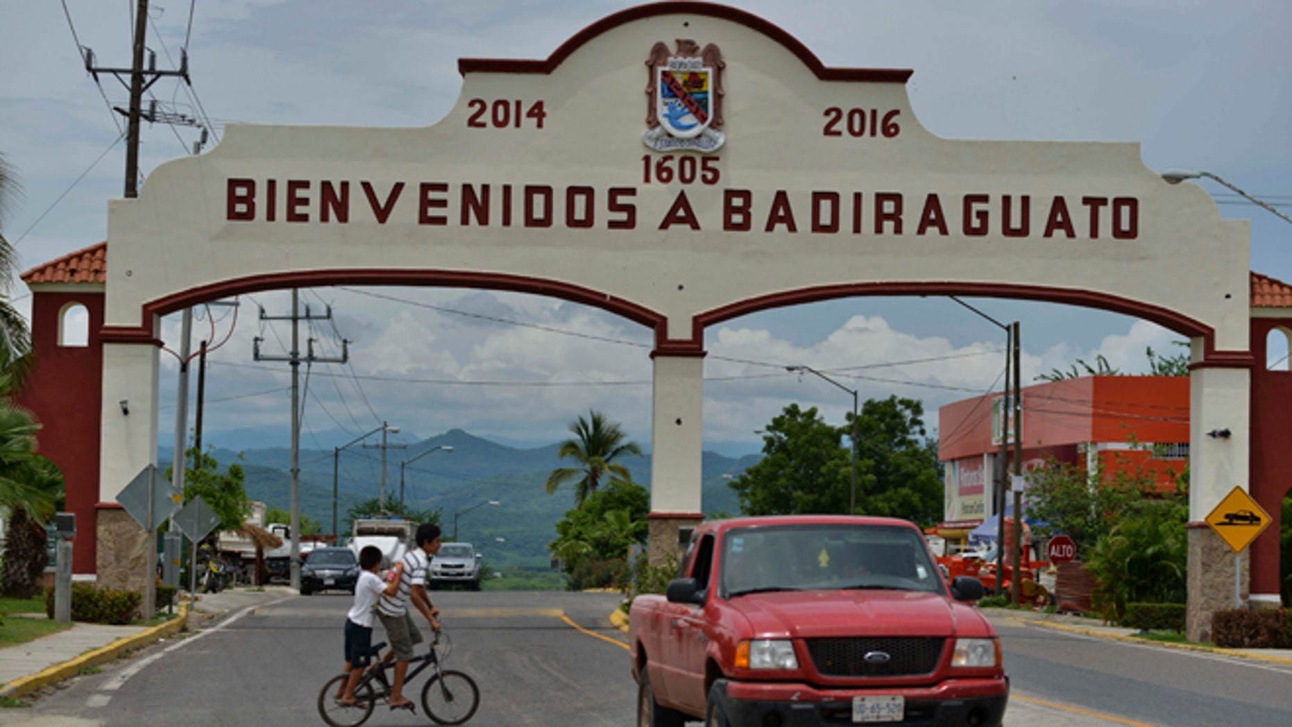 In this July 20, 2015 photo, a car drives past the entrance to the town of Badiraguato, Mexico.