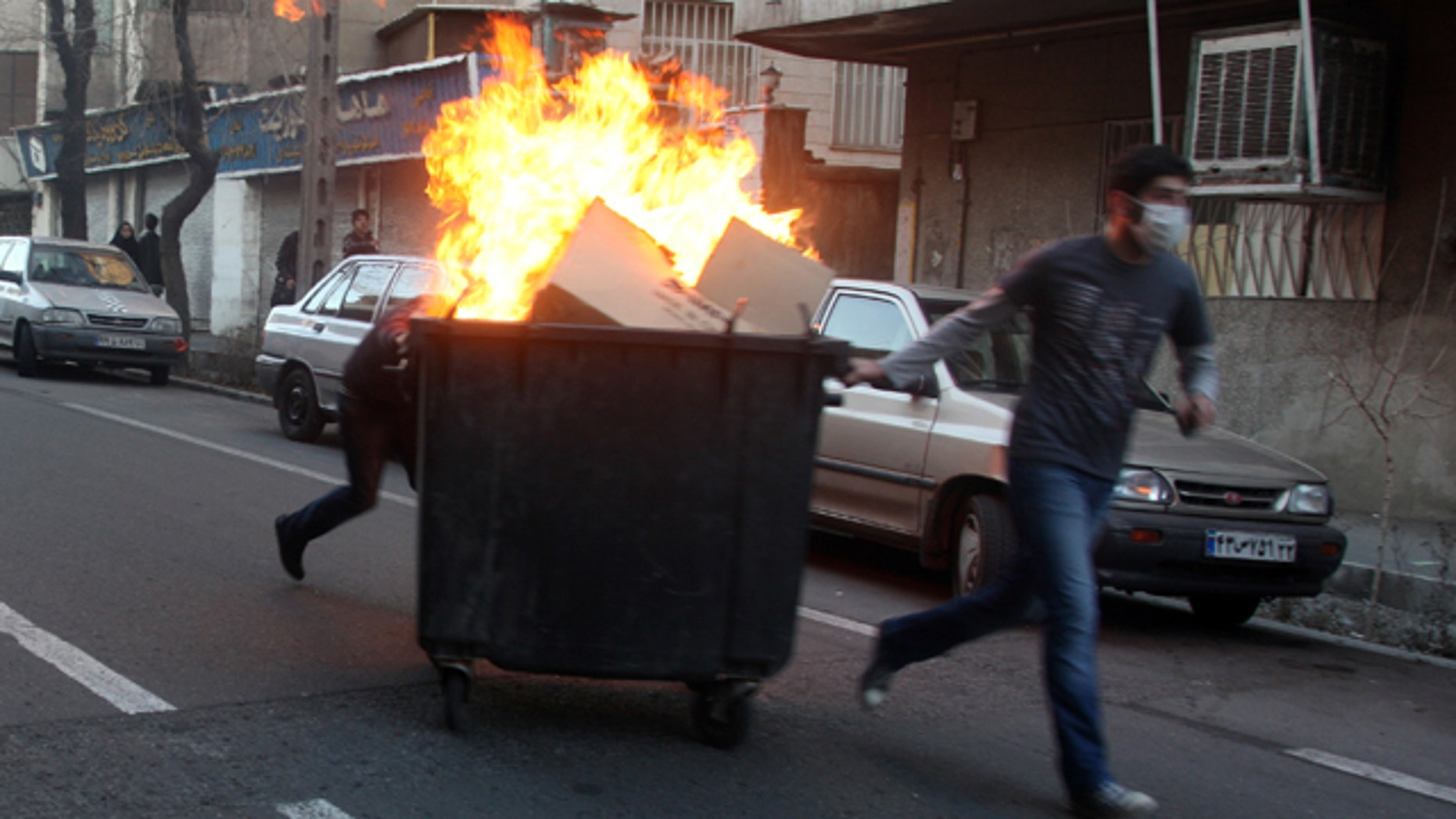Feb. 14: This photo, taken by an individual not employed by the Associated Press and obtained by the AP outside Iran, shows Iranian protestors moving a garbage can which is set on fire during an anti-government protest in Tehran, Iran.