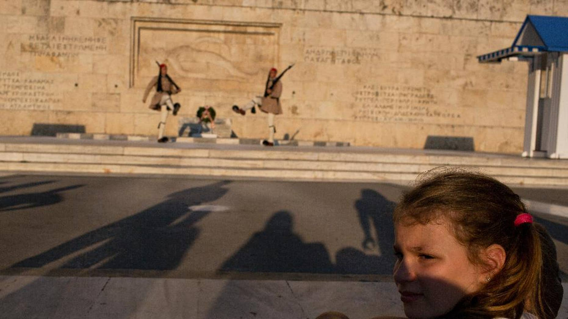 A visitor looks away from the changing of the guard ceremony at Greece's parliament to watch a small number of protesters across the street, in central Athens on Tuesday, July 5, 2016. The tiny anti-government rally was held to mark a year since Greeks voted against bailout measures in a referendum. Shortly after the vote, Greece reaching a third bailout deal with international rescue creditors. (AP Photo/Petros Giannakouris)