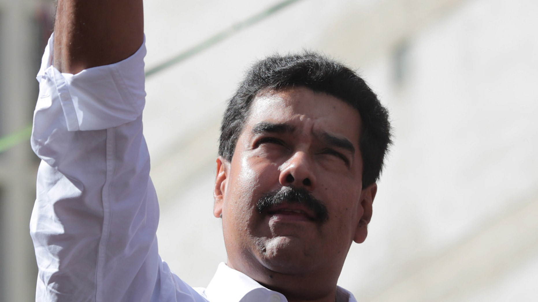In this photo provided by Miraflores Presidential Press Office, Venezuela's President Nicolas Maduro holds up fist in solidarity at a transport workers rally in Caracas, Venezuela, Tuesday, Nov. 12, 2013. Maduro says he'll present evidence in the coming hours showing how the U.S. Embassy in Caracas is plotting to destabilize the South American nation. Maduro's announcement at a pro-government rally Tuesday comes after he vowed to extend price caps that have led to long lines of bargain hunters at appliance stores across the country in recent days. (AP Photo/Miraflores Presidential Office)