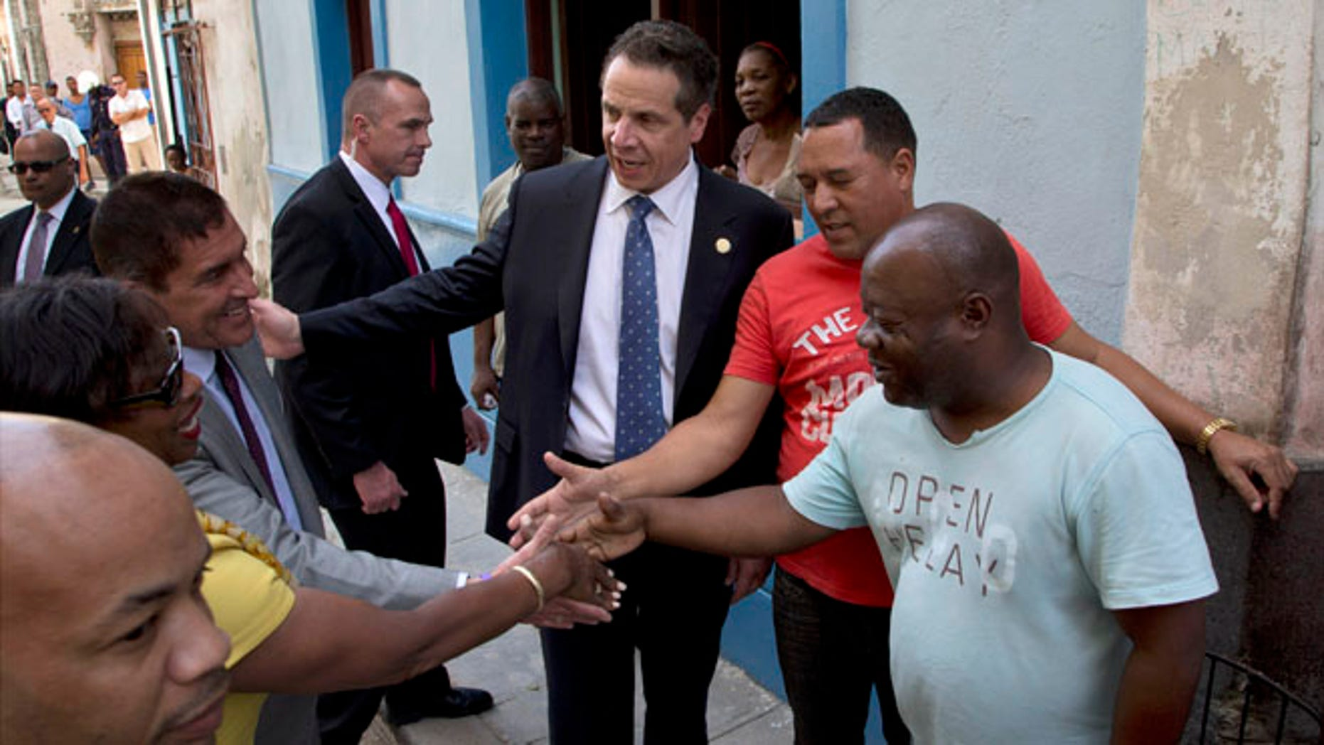 New York Governor Andrew Cuomo, center, greets people on a street  in old Havana, Cuba, Monday, April 20, 2015. The formal state visit, a trip that makes Cuomo the first American governor to visit the island since the recent thaw in relations with the communist nation, is meant to foster greater ties between New York and Cuba. (AP Photo/Ramon Espinosa)