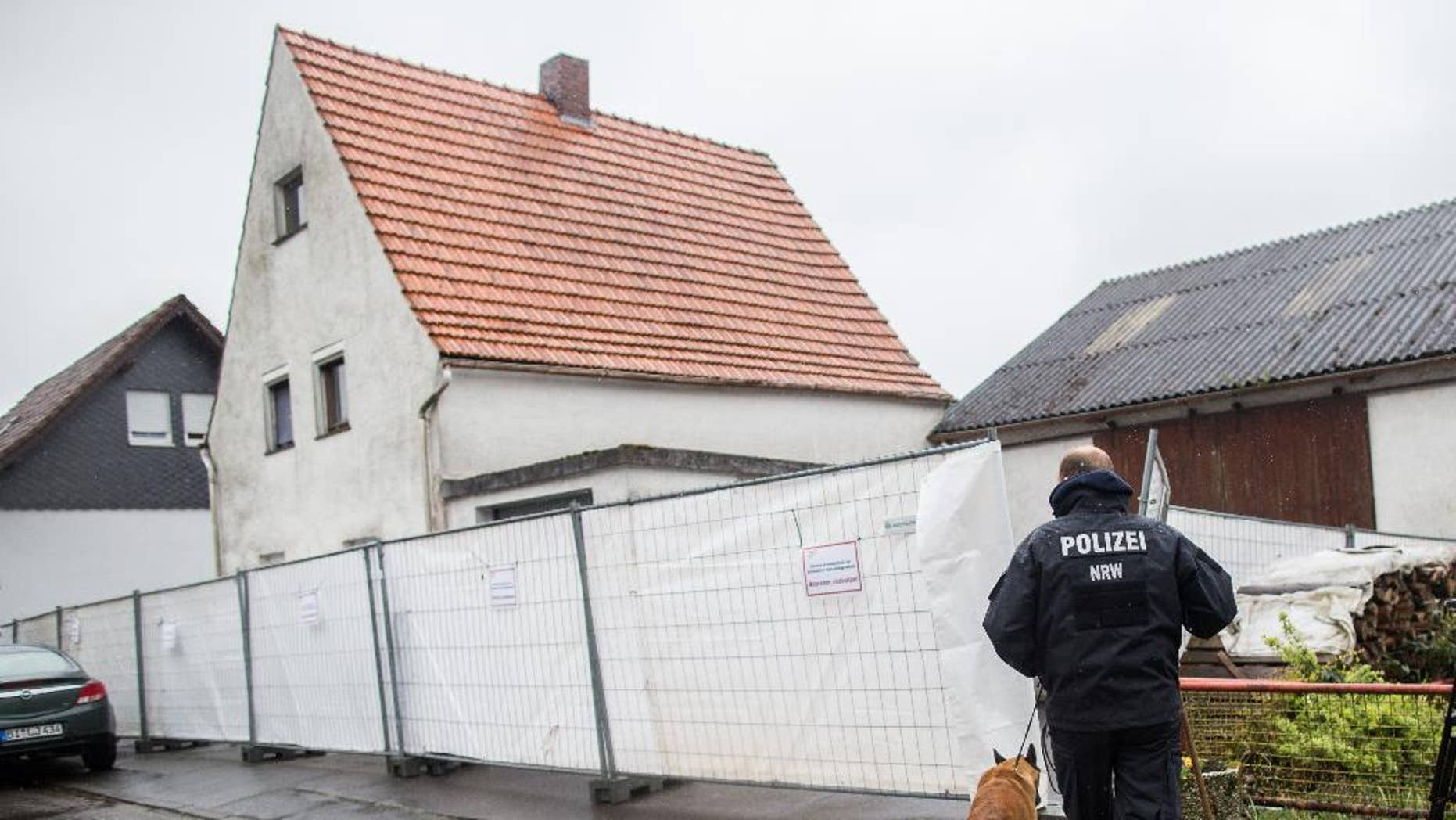 FILE - This is a Tuesday, May 3, 2016 file photo of a police officer with a dog as they pass by a house outside Hoexter, western Germany. German police say they have identified at least four women who survived abuse in the home of a couple suspected of killing two other women. Police said Monday May 9, 2016 that they have contacted the survivors, including a woman from the Berlin area who told investigators she was imprisoned for about three months in the house near the western town of Hoexter. (Marcel Kusch/dpa via AP) GERMANY OUT AUSTRIA OUT SWITZERLAND OUT