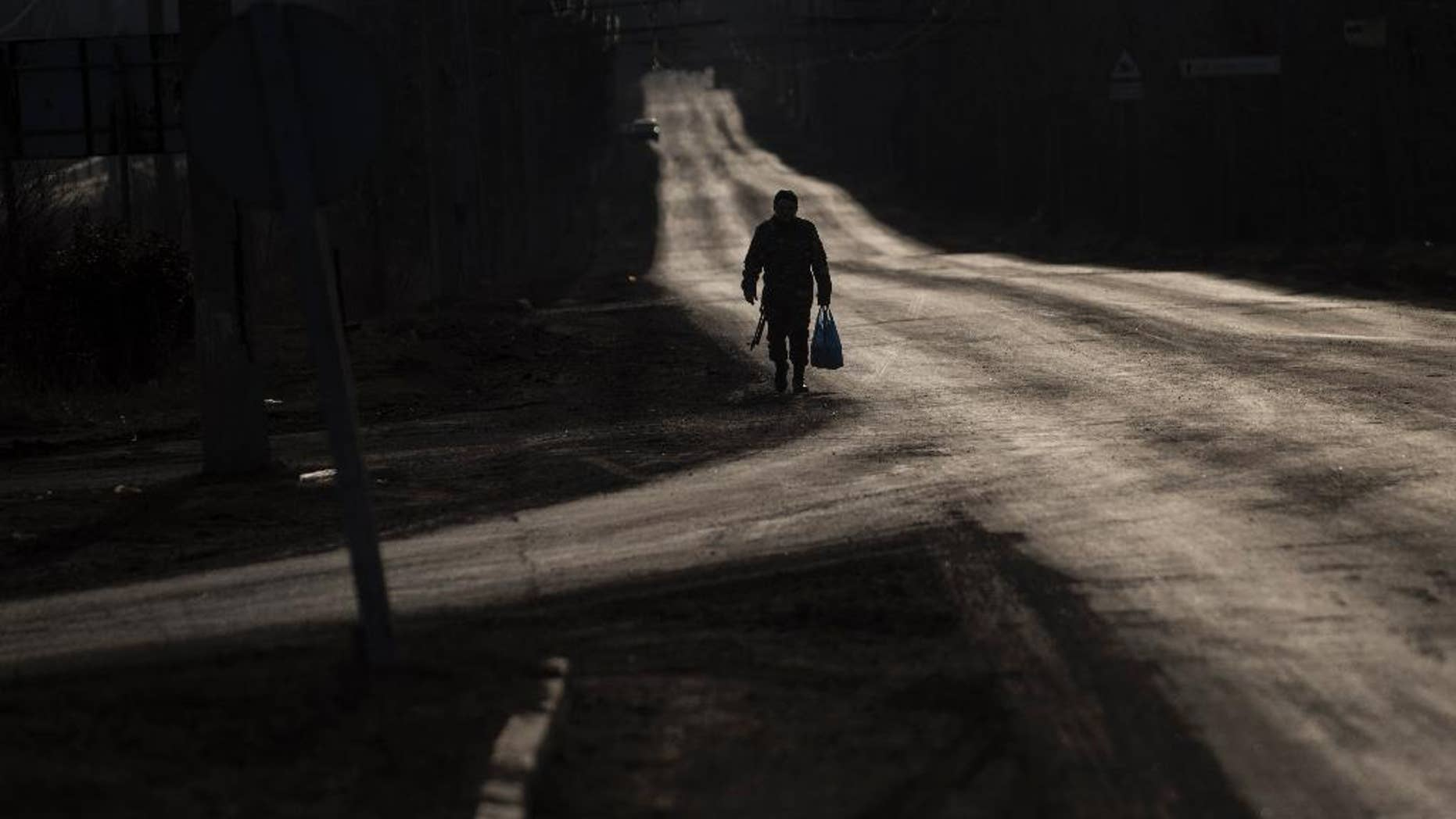 A Ukrainian serviceman walks on an empty road near Artemivsk, eastern Ukraine, Friday, March 6, 2015. Ukrainian military officials say government forces are withdrawing heavy rocket launchers from the front line with Russian-backed separatists in accordance with last month's cease-fire accord. (AP Photo/Evgeniy Maloletka)