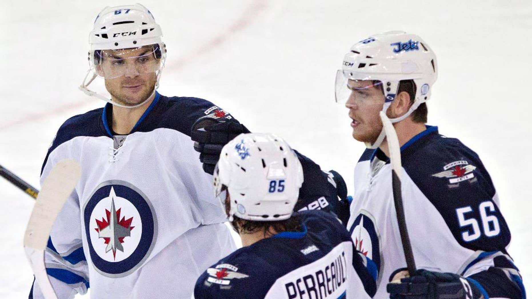 Winnipeg Jets Michael Frolik (67), Mathieu Perreault (85)and Adam Lowry (56) celebrate a goal against the Edmonton Oilers during second period NHL hockey action in Edmonton, Alberta, on Monday, Sept. 29, 2014.(AP Photo/The Canadian Press, Jason Franson)