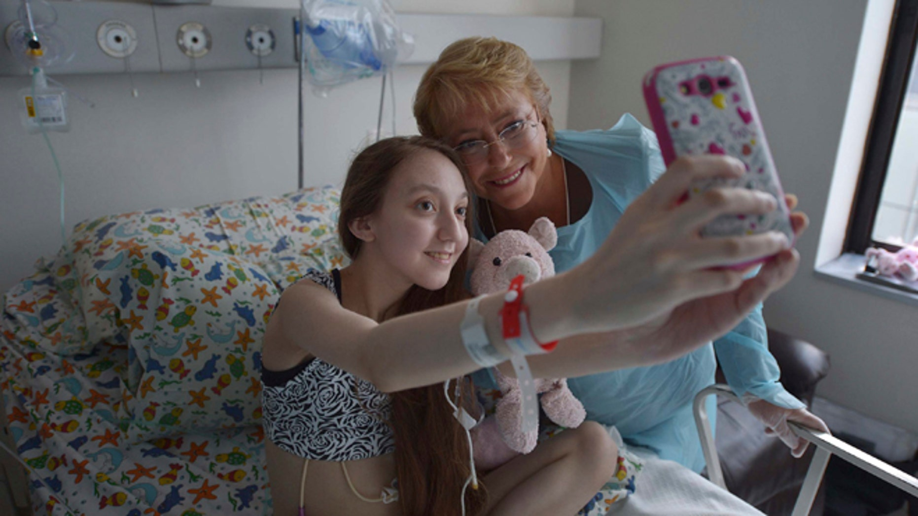 In this Feb 28, 2015 photo released by Chile's Presidential Press Office, Valentina Maureira takes a photo of herself with President Michelle Bachelet, at the Catholic University hospital in Santiago, Chile. The ailing 14-year-old released a video last month in which she asked Bachelet to allow her to be euthanized. Bachelet visited the girl and her family but the government said it could not approve her request. Valentina's father said Sunday, March 22, that people who responded to her plea have led her to change her mind despite her suffering from cystic fibrosis. (AP Photo/Chile Presidential Press Office, Ximena Navarro)