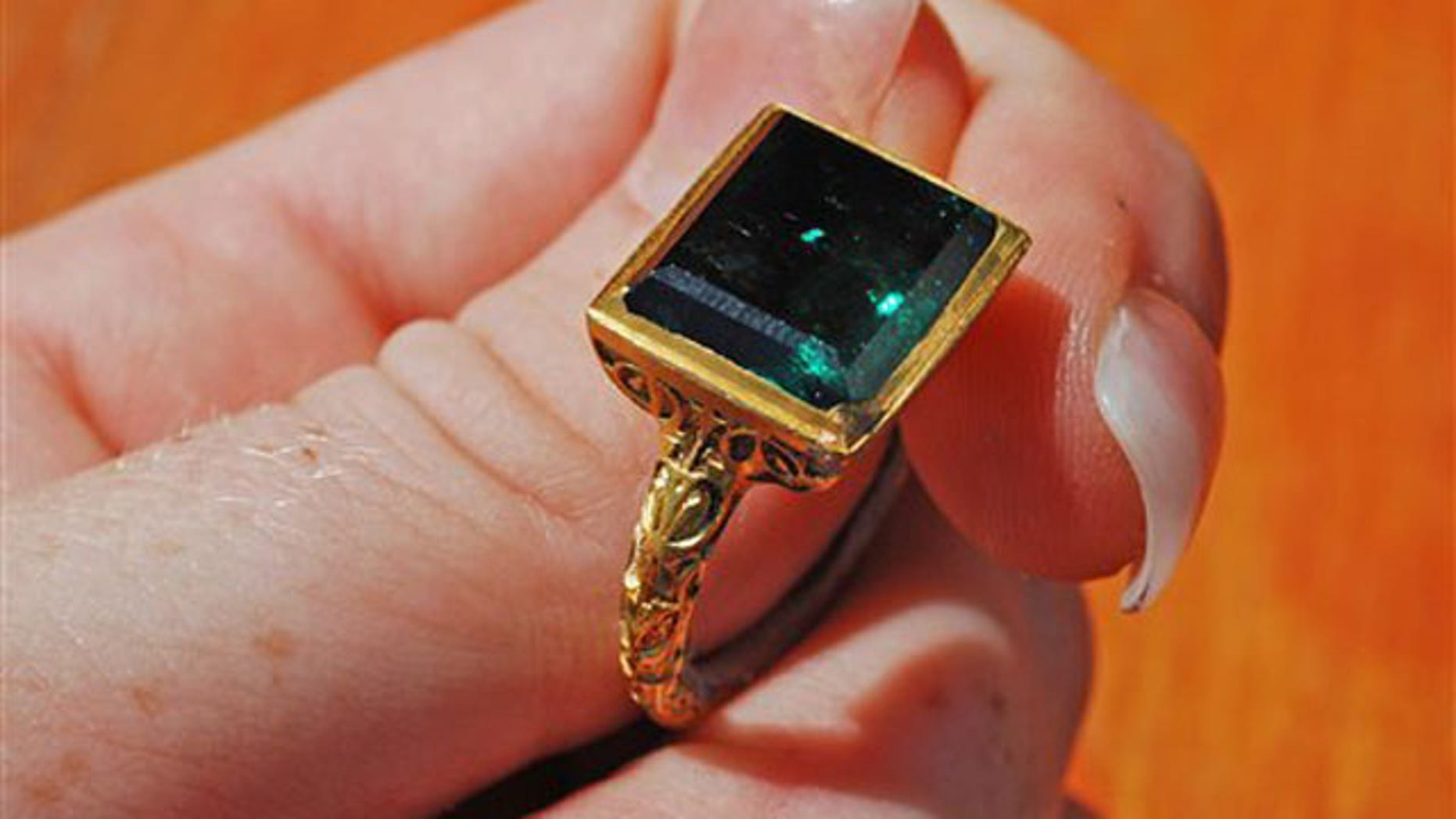 In this photo released by the Florida Keys News Bureau, an ancient gold ring with a rectangular cut emerald, believed to be from the Spanish galleon Nuestra Senora de Atocha that sank off the Florida Keys during a 1622 hurricane, is displayed Thursday, July 23, 2011, about 35 miles west of Key West, Fla. Divers from Mel Fisher's Treasures, searching for the sterncastle of the Atocha, said they found the ring Thursday. Its estimated value is $500,000. (AP Photo/Florida Keys News Bureau, Sharon Wiley)
