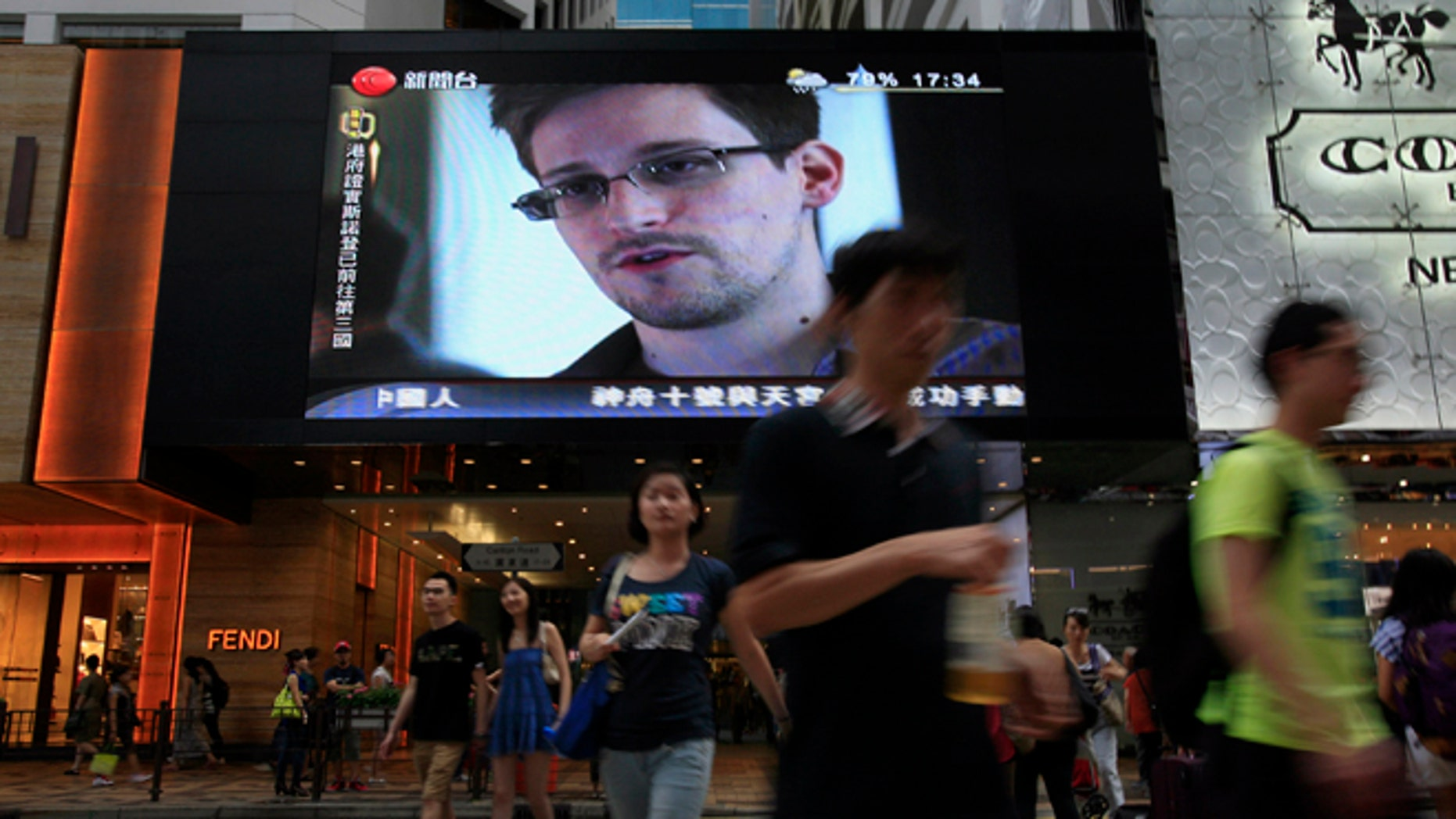 FILE - This June 23, 2013 file photo shows a TV screen shows a news report of Edward Snowden, a former CIA employee who leaked top-secret documents about sweeping U.S. surveillance programs, at a shopping mall in Hong Kong. The saga of Edward Snowden and the NSA makes one thing clear: The United States' central role in developing the Internet and hosting its most powerful players has made it the global leader in the surveillance game . Other countries, from dictatorships to democracies, are also avid snoopers, tapping into the high-capacity fiber optic cables to intercept Internet traffic, scooping their citizens' data off domestic servers, and even launching cyberattacks to win access to foreign networks. (AP Photo/Vincent Yu, File)