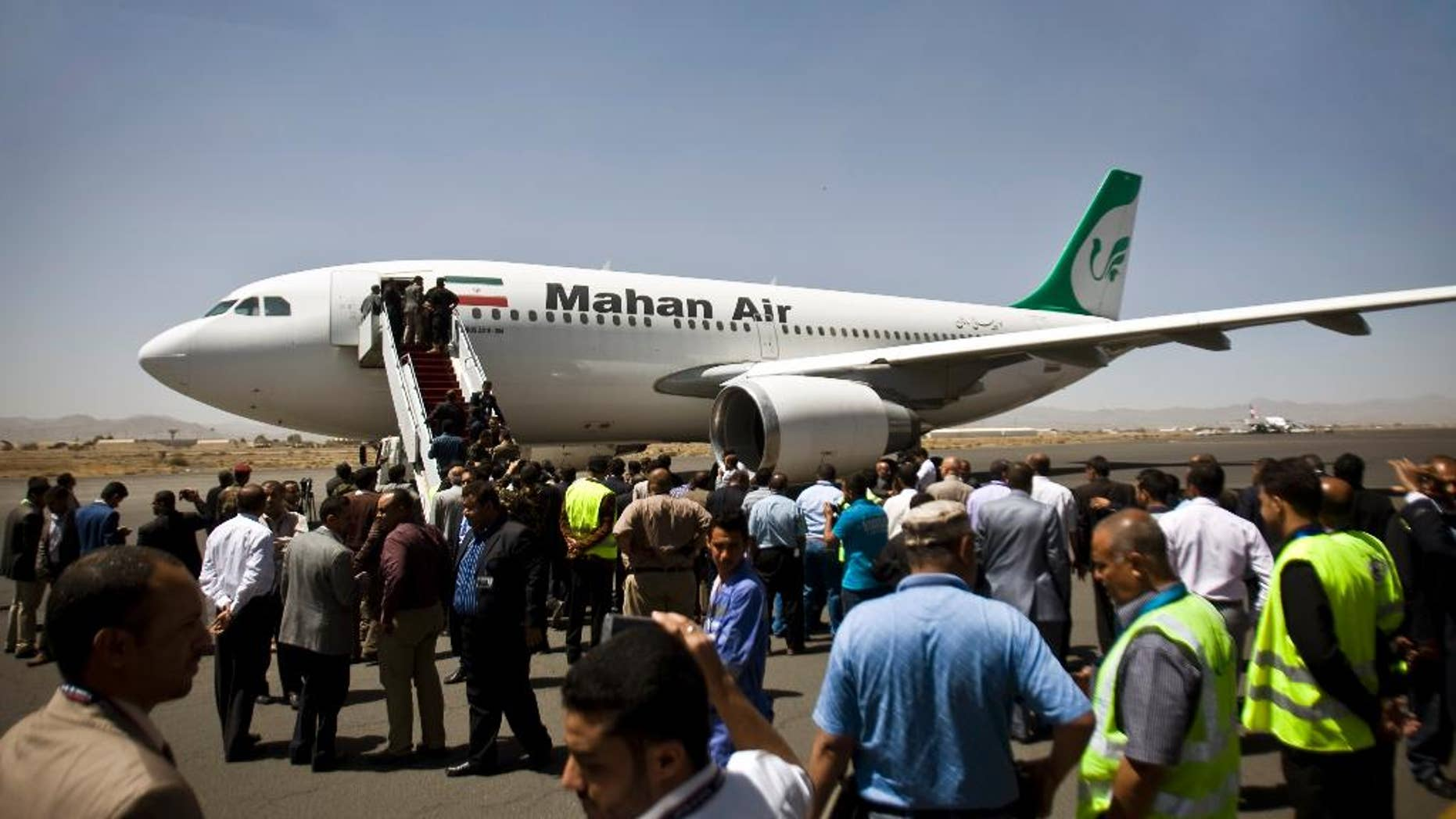 "FILE -- In this March 1, 2015 file photo, Yemeni airport, security and transportation officials greet a plane from the Iranian private airline, Mahan Air after it lands in Sanaa, Yemen. Saudi Arabia's General Authority of Civil Aviation issued an order in a statement Monday, April 4, 2016, that banned Mahan Air from flying into the kingdom  over ""systematic violations"" of the country's safety regulations and laws as tensions between the two Mideast powers remain high. (AP Photo/Hani Mohammed, File)"