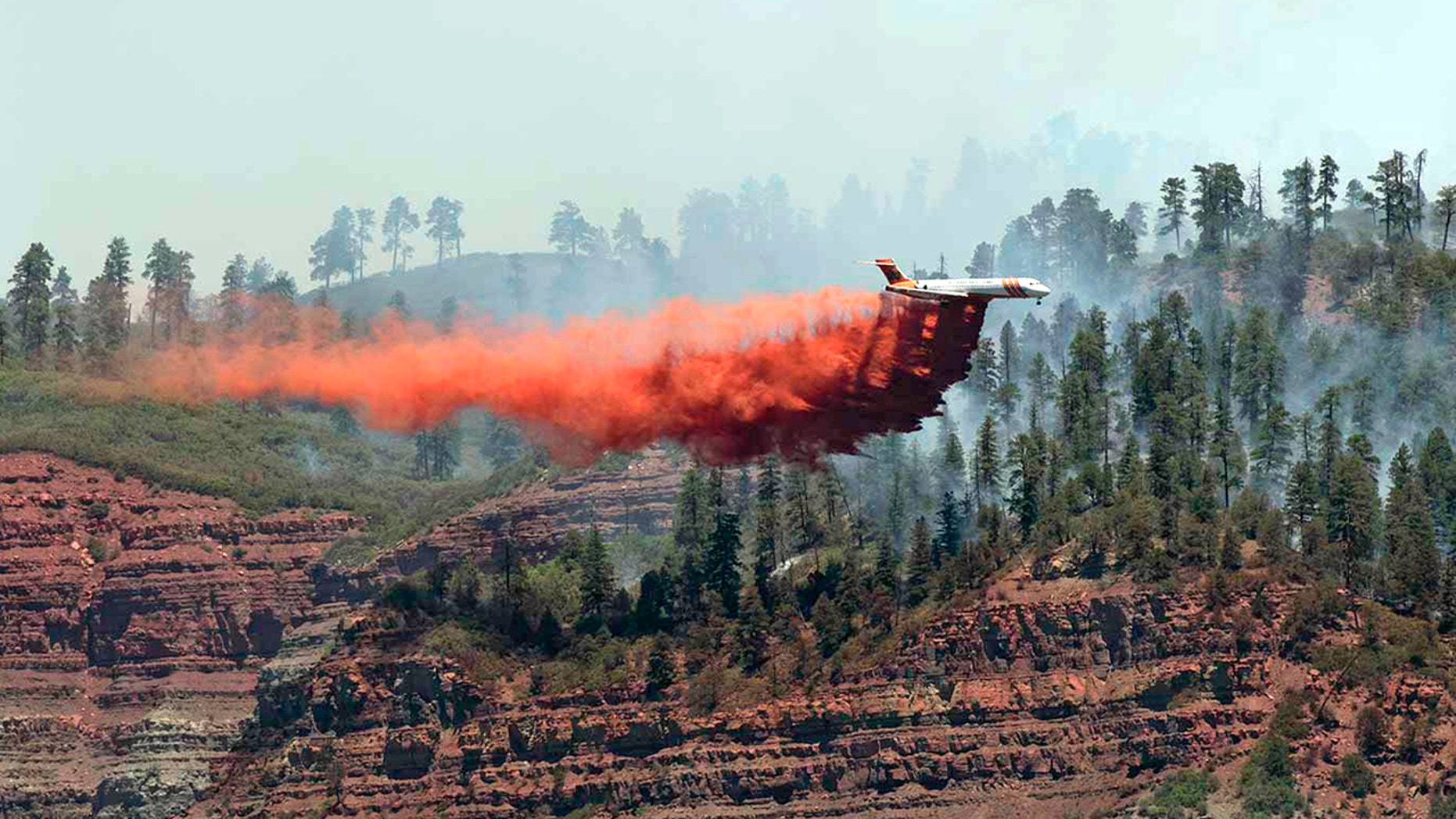 In this photo provided by Jerry Day, an aircraft makes a fire retardant drop on a wildfire in the hills and forests near Durango, Colo., on Friday.