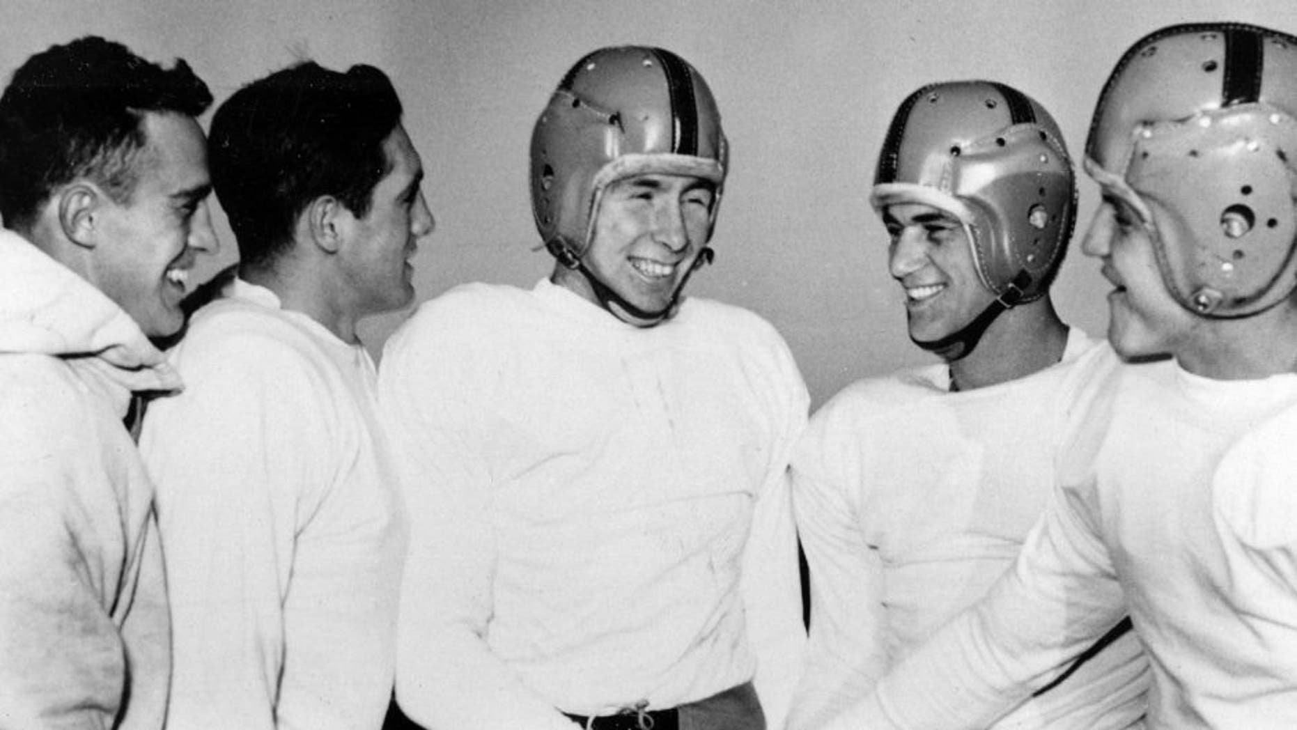 FILE - In this Dec. 11, 1953, file photo, Notre Dame player John Lattner, center, winner of the 1953 Heisman tropy and second-time winner of the Maxwell trophy, receives congratulations from teammates at practice in South Bend, Ind. Lattner, who helped lead Notre Dame to a 9-0-1 record and a No. 2 ranking in Frank Leahy's final year as coach, has died at 83. His death was confirmed Saturday, Feb. 13, 2016, by Notre Dame. (AP Photo/File)