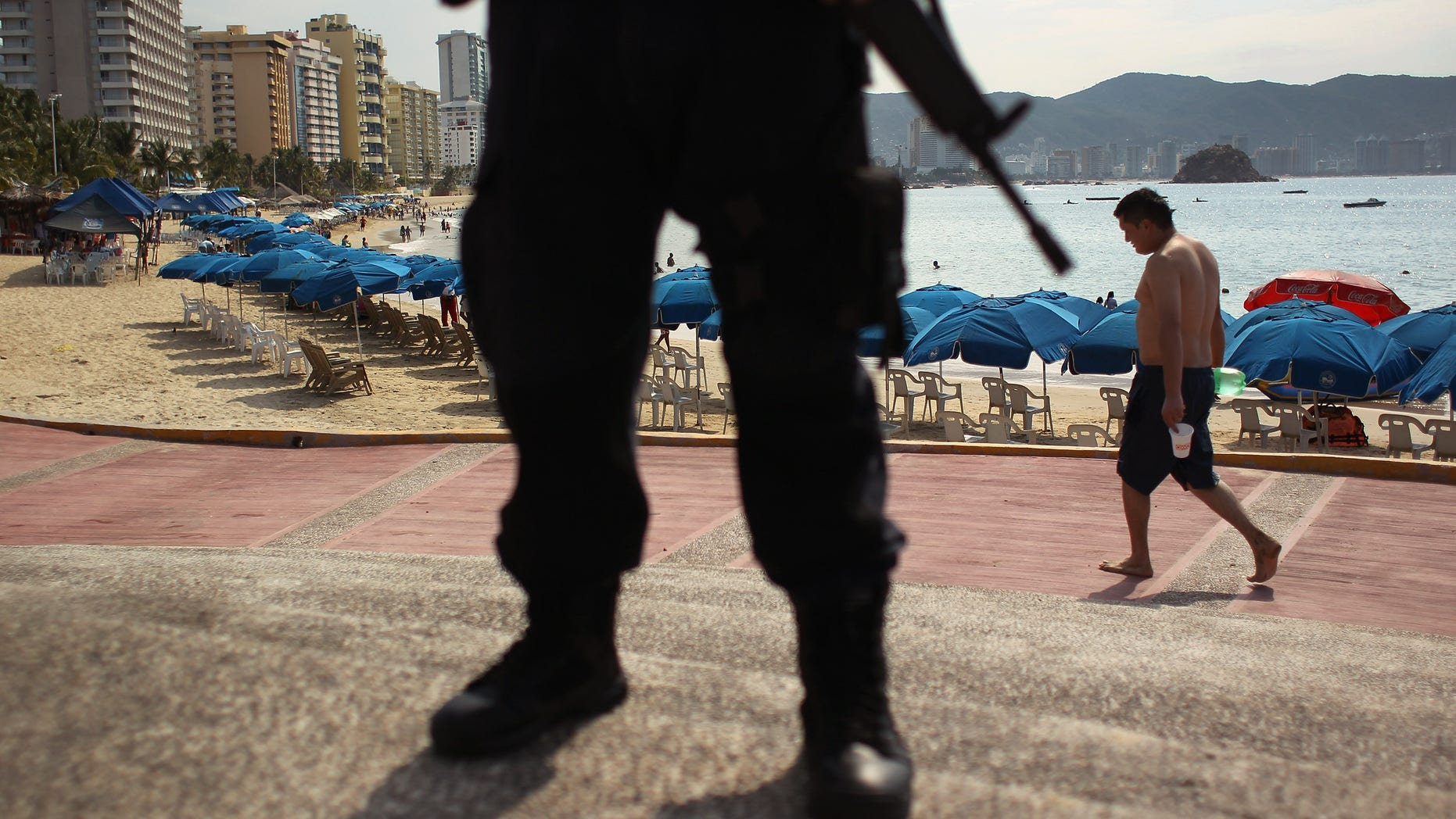 A Mexican federal policeman stands guard near the beach in Acapulco, Mexico.