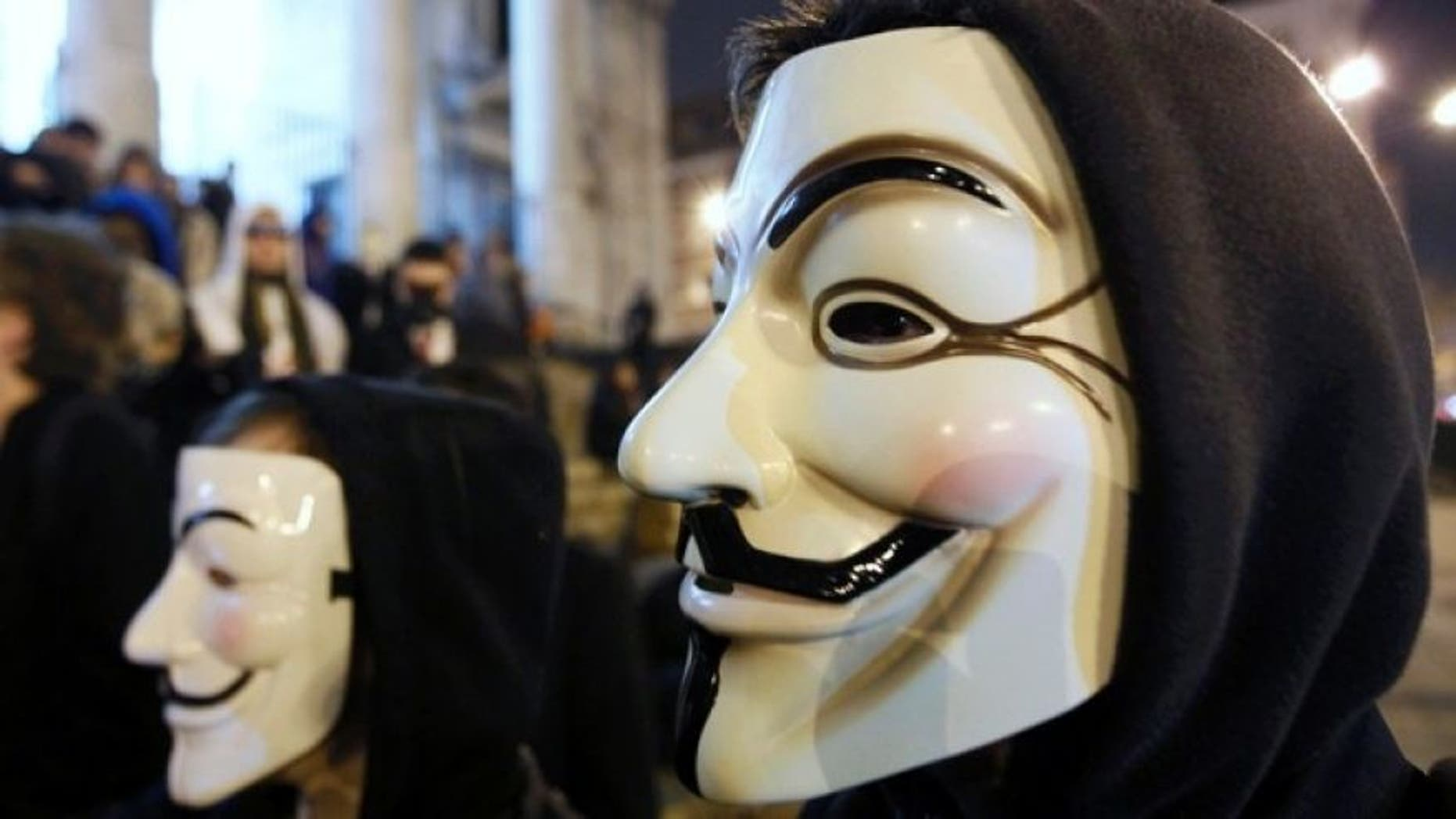 """Jan. 28, 2012: A protester wearing a Guy Fawkes mask, symbolic of the hacktivist group """"Anonymous"""", takes part in a protest in central Brussels."""
