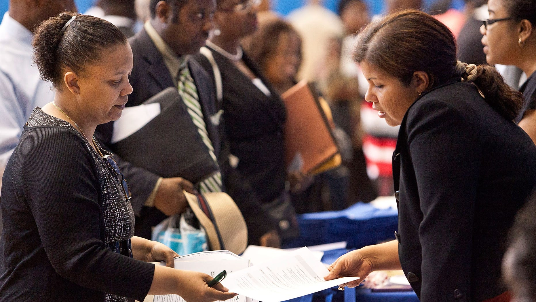 """NEW YORK, NY - JUNE 07:  A woman speaks to a potential employer at a New York state jobs fair in the Harlem Armory on June 7, 2012 in New York City. The job fair was put together by the New York State Department of Labor and New York State assemblyman Keith Wright. The U.S. Department of Labor has coined the month of June as """"Jobs Fair Month.""""  (Photo by Andrew Burton/Getty Images)"""