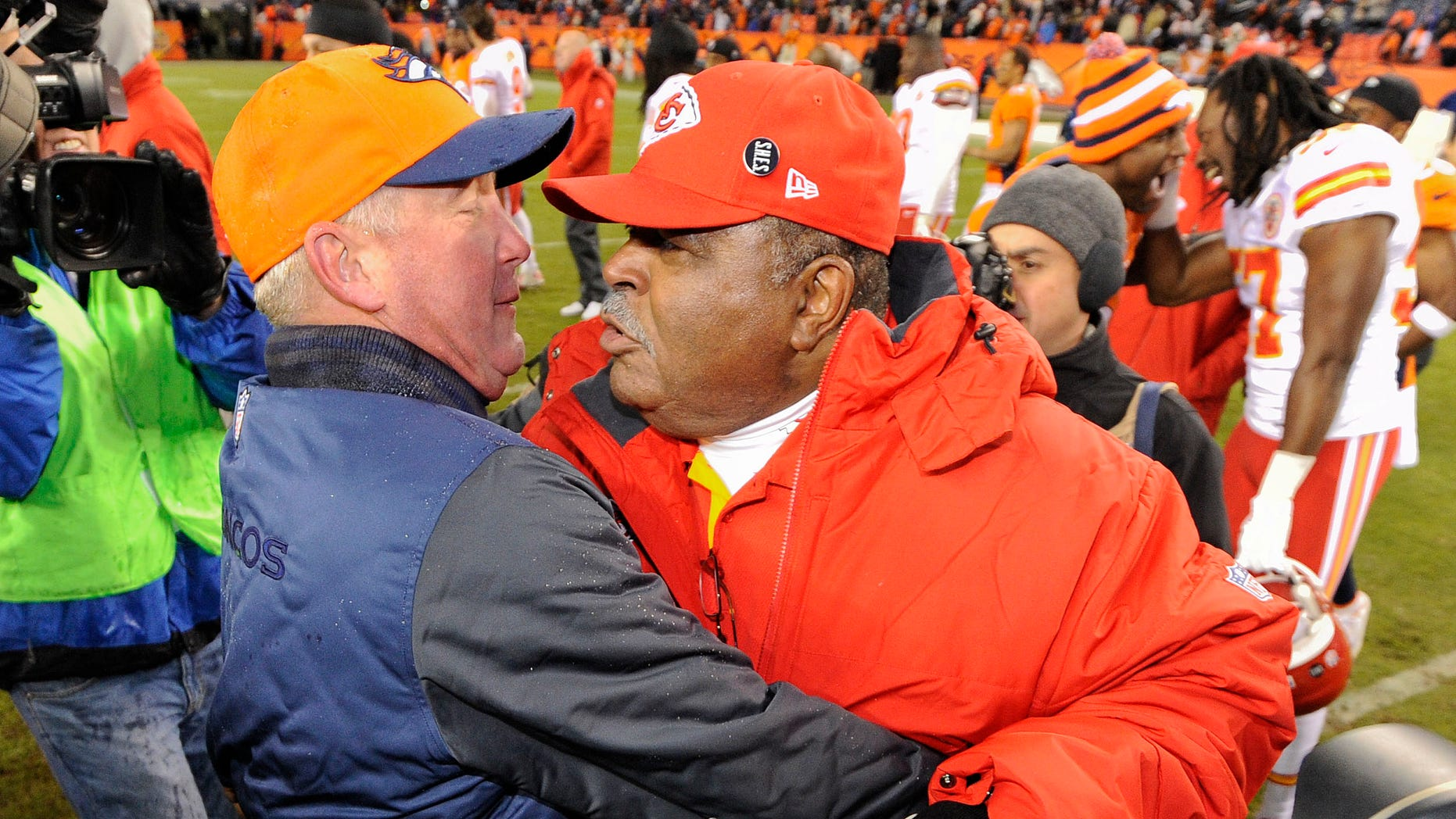 Denver Broncos head coach John Fox, left, greets Kansas City Chiefs coach Romeo Crennel at the end of an NFL football game, Sunday, Dec. 30, 2012, in Denver. Denver won 38-3. (AP Photo/Jack Dempsey)