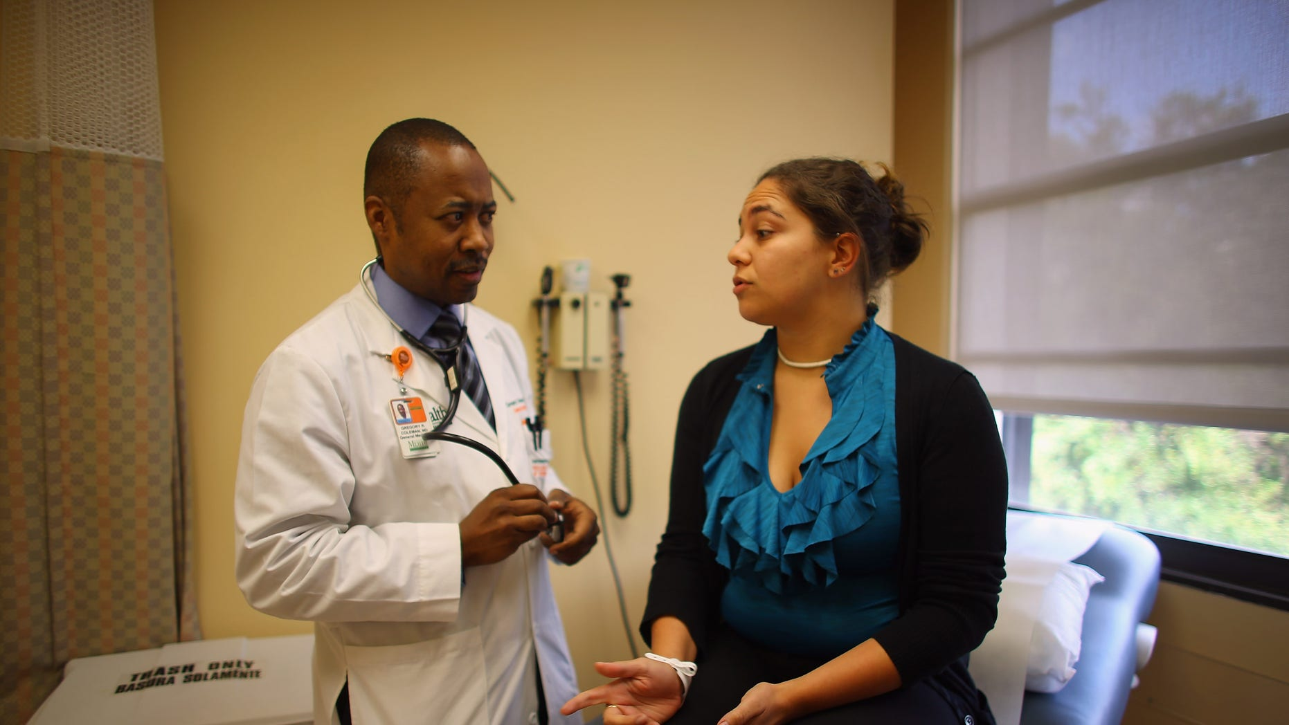 MIAMI, FL - JUNE 28:  Dr. Gregory Coleman, Assistant Professor of Medicine, University of Miami, Miller School of Medicine, speaks with Vanessa Moreno, 25 years old, as she visits him for a check-up on the same day that the United States Supreme Court upheld the Affordable Care Act on June 28, 2012 in Miami, Florida. Dr. Coleman said, ?the ruling is a good start to begin to control the economics of medicine?.  (Photo by Joe Raedle/Getty Images)