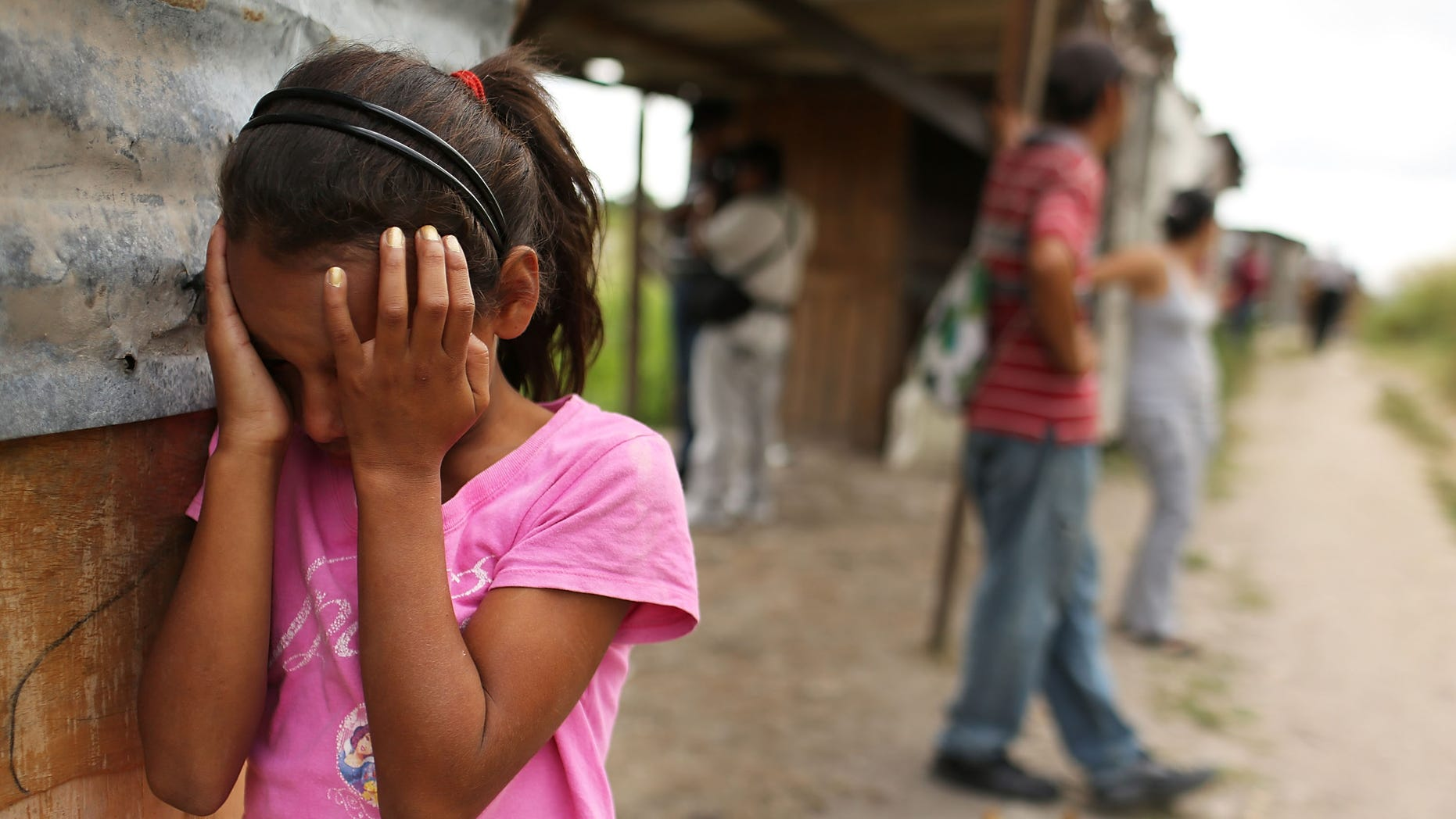 TEGUCIGALPA, HONDURAS - JULY 20:  A young girl cries as her home and neighborhood are forcefully dismantled in a shanty town after the government claimed that the settlement was illegal on July 20, 2012 in Tegucigalpa, Honduras. Land disputes are becoming increasingly frequent in Honduras  which is alarming the nation's business class while sowing fears of increased political violence. In a nation where 72% of the poorest landowners hold only 11.6% of cultivated land, tensions are rising as the poor have few places to go and little opportunities for productive employment. Honduras now has the highest per capita murder rate in the world and its capital city, Tegucigalpa, is plagued by violence, poverty, homelessness and sexual assaults. With an estimated 80% of the cocaine entering the United States now being trans-shipped through Honduras, the violence on the streets is a spillover from the ramped rise in narco-trafficking.  (Photo by Spencer Platt/Getty Images)