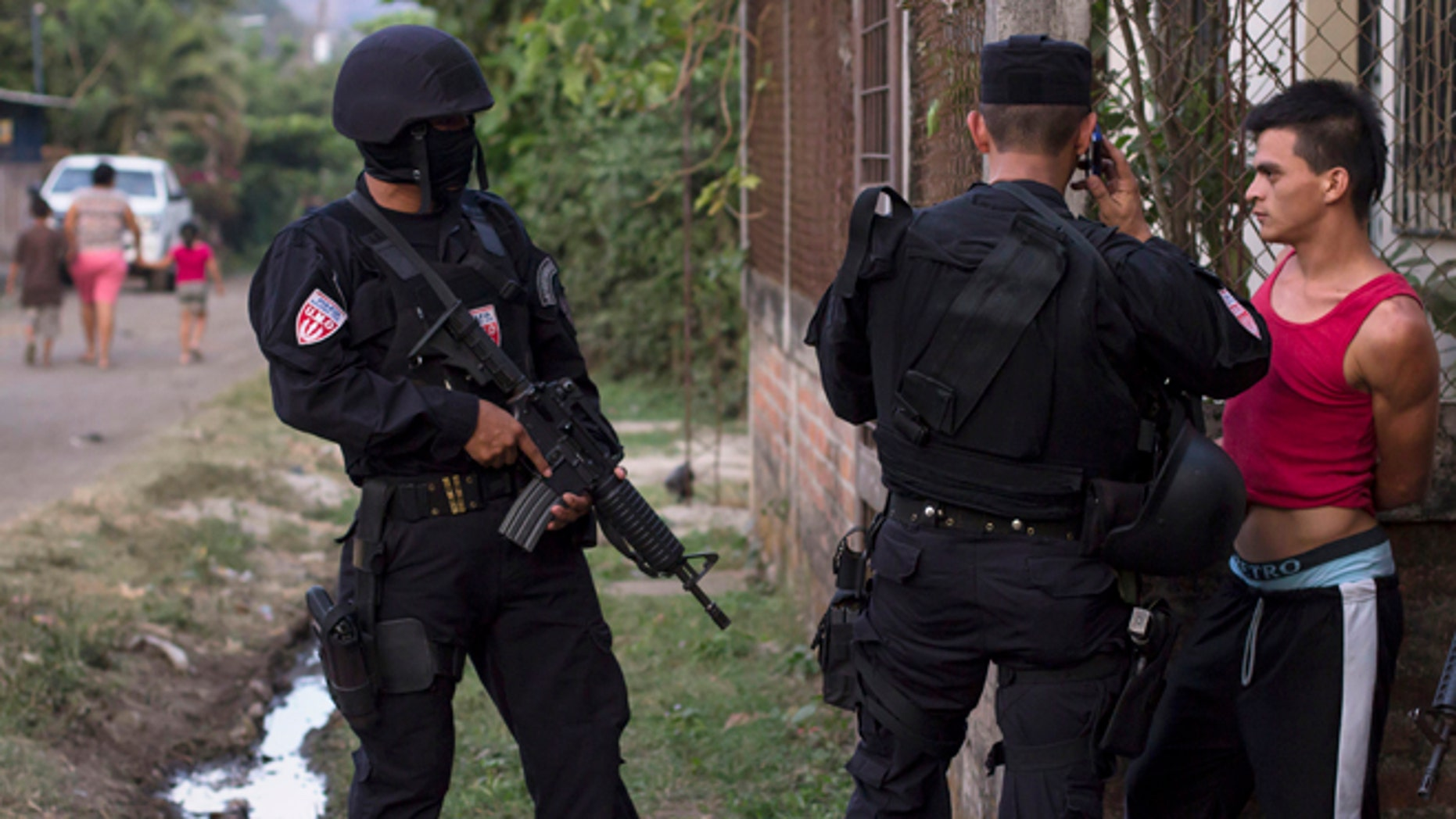 In this April 1, 2015 photo, a man is detained by police special forces in the town of San Juan Opico, El Salvador.
