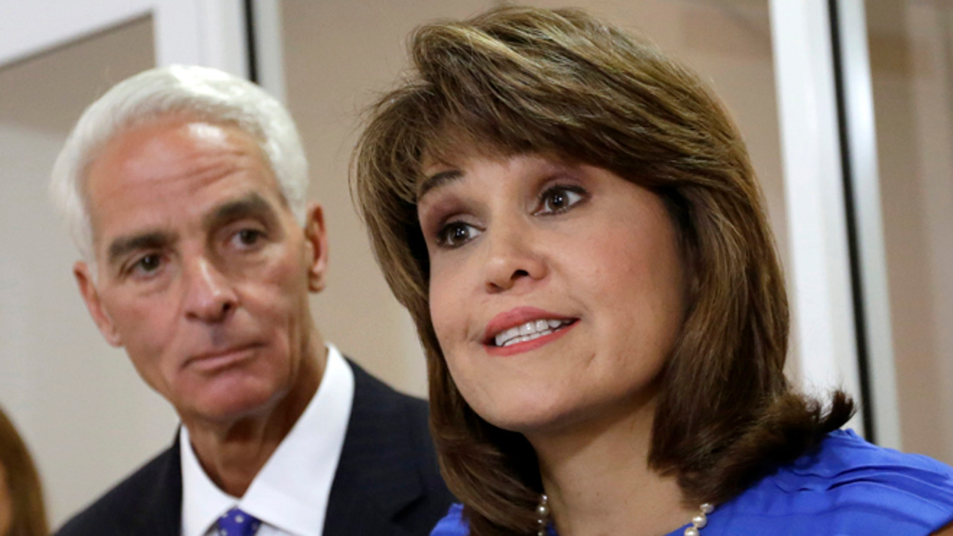 FILE - In this July 17, 2014 file photo, Annette Taddeo-Goldstein, right, talks to reporters during a news conference as former Gov. Charlie Crist listens in Miami. Crist picked former congressional candidate and Miami-Dade County Democratic Party chairwoman Annette Taddeo-Goldstein as his running mate.  After years of running few Latinos for statewide posts, Democrats are building a bench that better reflects the support they have in the Hispanic community: more than twice as many Hispanics identify as Democrats than Republicans nationally, according to polls. This year they are showcasing this bench in key states that not only have large Hispanic electorates but enough electoral votes to swing presidential elections. The shift is crucial for a party that often fails to get its Hispanic supporters to the polls. (AP Photo/Alan Diaz)