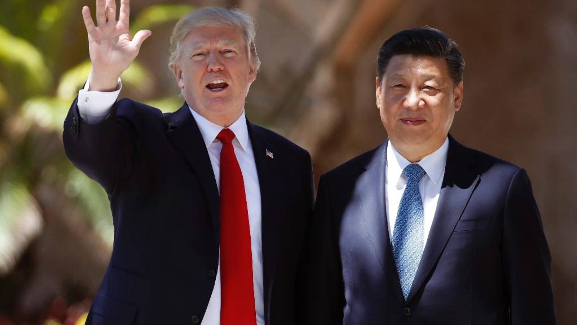 """FILE - In this Friday, April 7, 2017, file photo, U.S. President Donald Trump, left, and Chinese President Xi Jinping pause for photographs at Mar-a-Lago in Palm Beach, Fla. North Korea often marks significant dates by displaying military capability, and South Korean officials say there's a chance the country will conduct its sixth nuclear test or its maiden test launch of an ICBM around the founding anniversary of its military on Tuesday, April 25. Trump spoke by phone with both the Japanese and Chinese leaders Monday, April 24. China's official broadcaster CCTV quoted Xi telling Trump that China strongly opposed North Korea's nuclear weapons program and hoped """"all parties will exercise restraint and avoid aggravating the situation."""" (AP Photo/AlexBrandon, File)"""