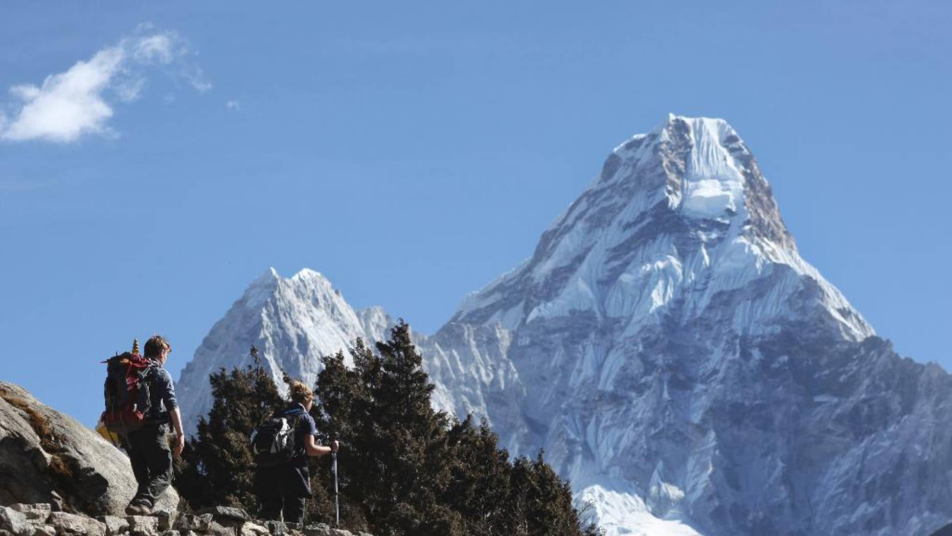 FILE - In this Feb. 19, 2016, file photo, trekkers make their way to Dingboche, a popular Mount Everest base camp, in Pangboche, Nepal. Officials say three foreign climbers; two British Kenton Cool, Robert Richard Lucas, and Mexican David Liano Gonzalez along with three Nepalese guides have scaled Mount Everest, the first foreigners to reach the summit in two years. (AP Photo/Tashi Sherpa, File)