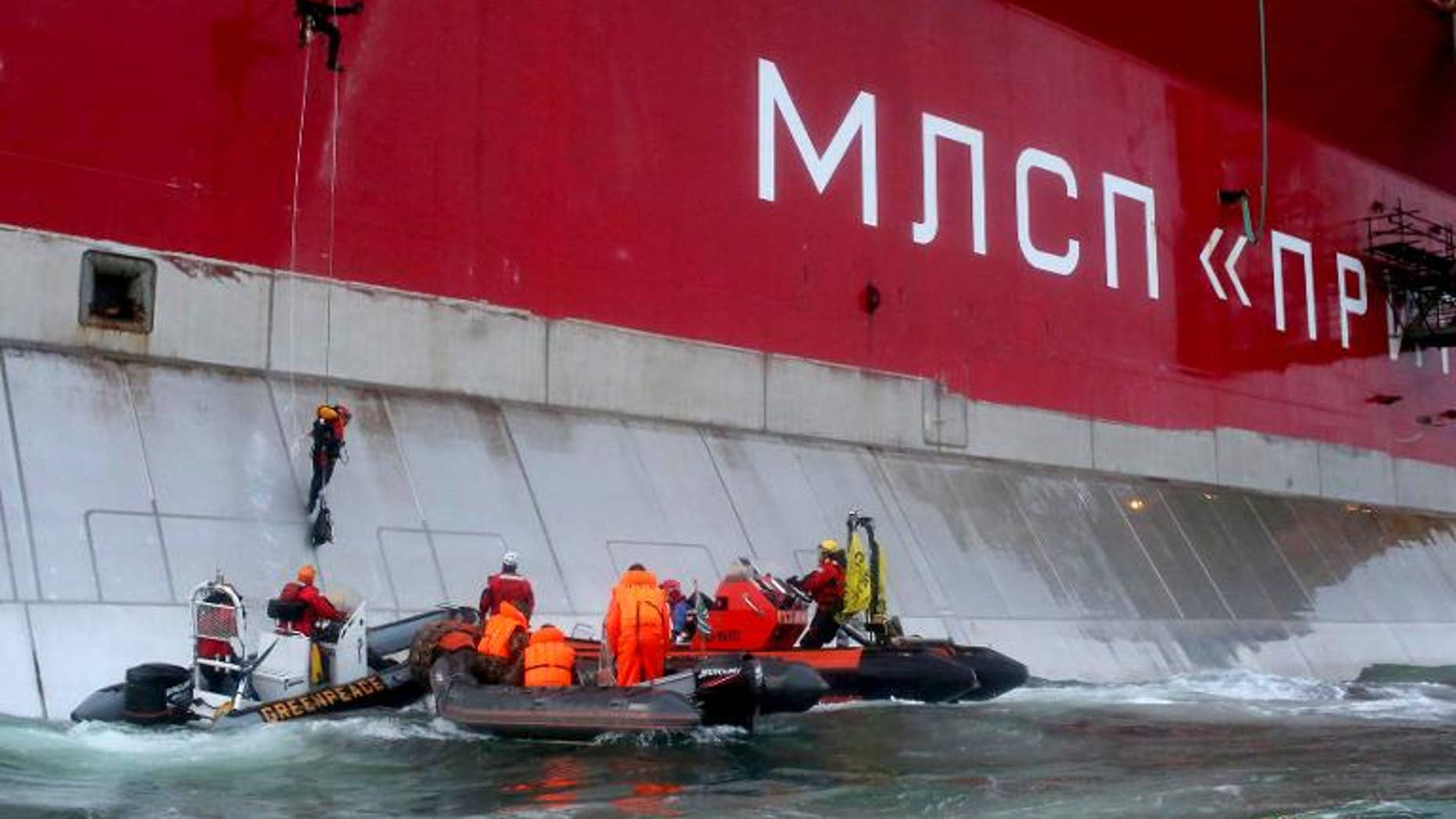 A photo taken by Greenpeace on September 18, 2013, shows Greenpeace activists boarding Gazprom??s ??Prirazlomnaya?? Arctic oil platform somewhere off Russia north-eastern coast in the Pechora Sea.