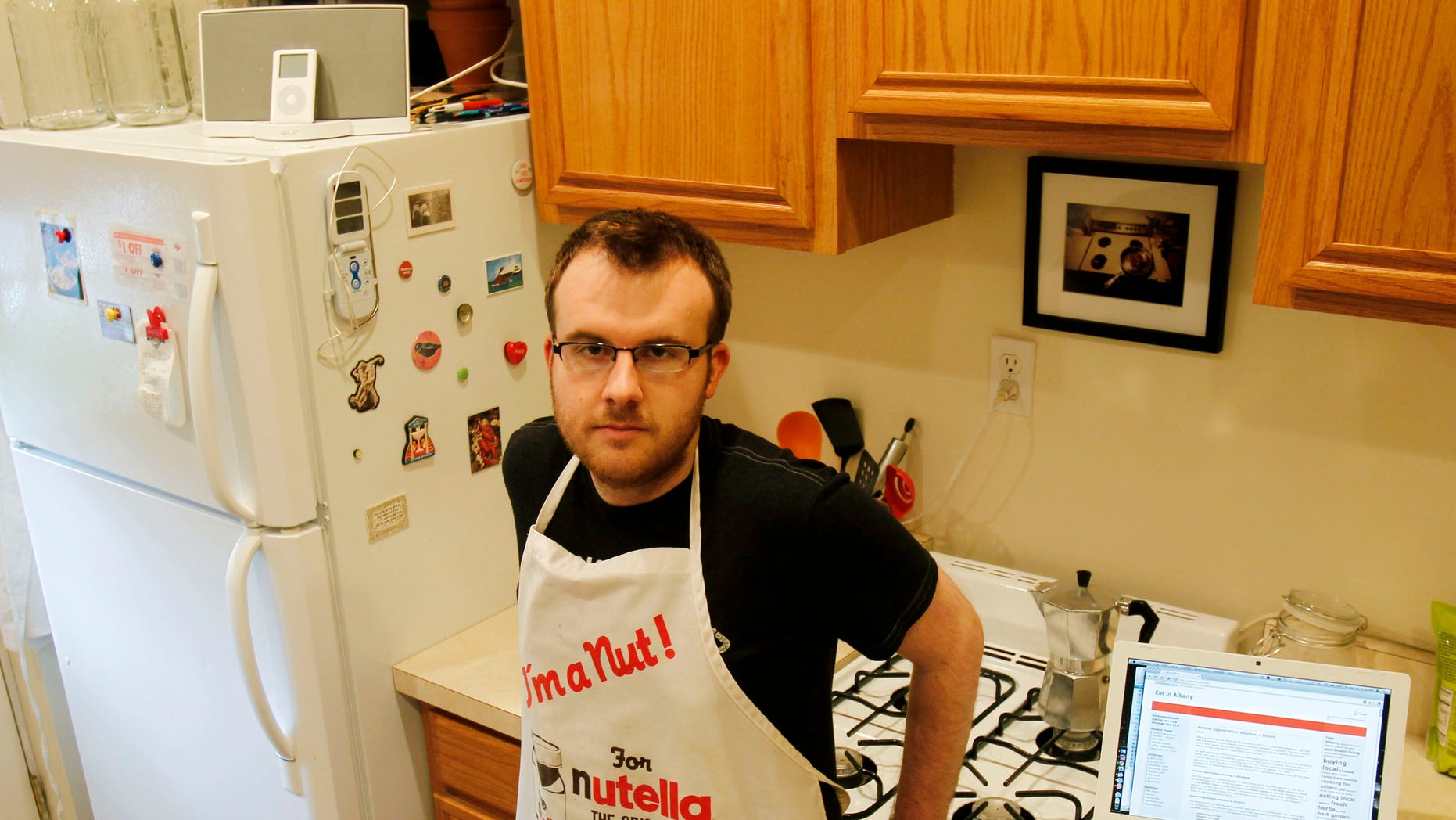 """Brian Kraus, who hosts a food blog, poses in his kitchen in Albany, N.Y., on Friday, April 30, 2010. Kraus loves to cook but has only one cookbook. When Kraus wanted tips on preparing a whole fish, he headed to the Web and did a """"mishmash"""" of stuff he liked from different sites.   (AP Photo/Mike Groll)"""