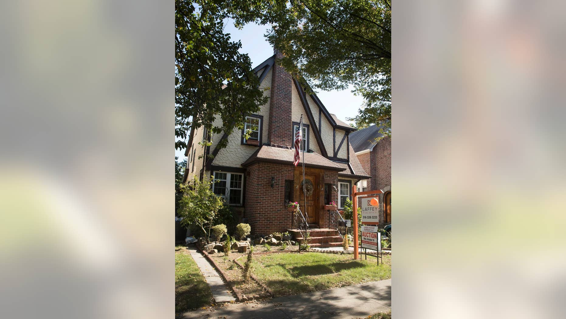 FILE - This Tuesday, Oct. 18, 2016 file photo, shows the exterior of a house in the Jamaica Estates neighborhood of the Queens borough of New York, where Republican presidential candidate Donald Trump spent his early childhood. Trump's boyhood home in New York City is going back on the auction block. Paramount Realty said the 1940 Tudor-style house in Jamaica Estates in Queens is being offered Jan. 17, 2017. (AP Photo/Mary Altaffer, File)