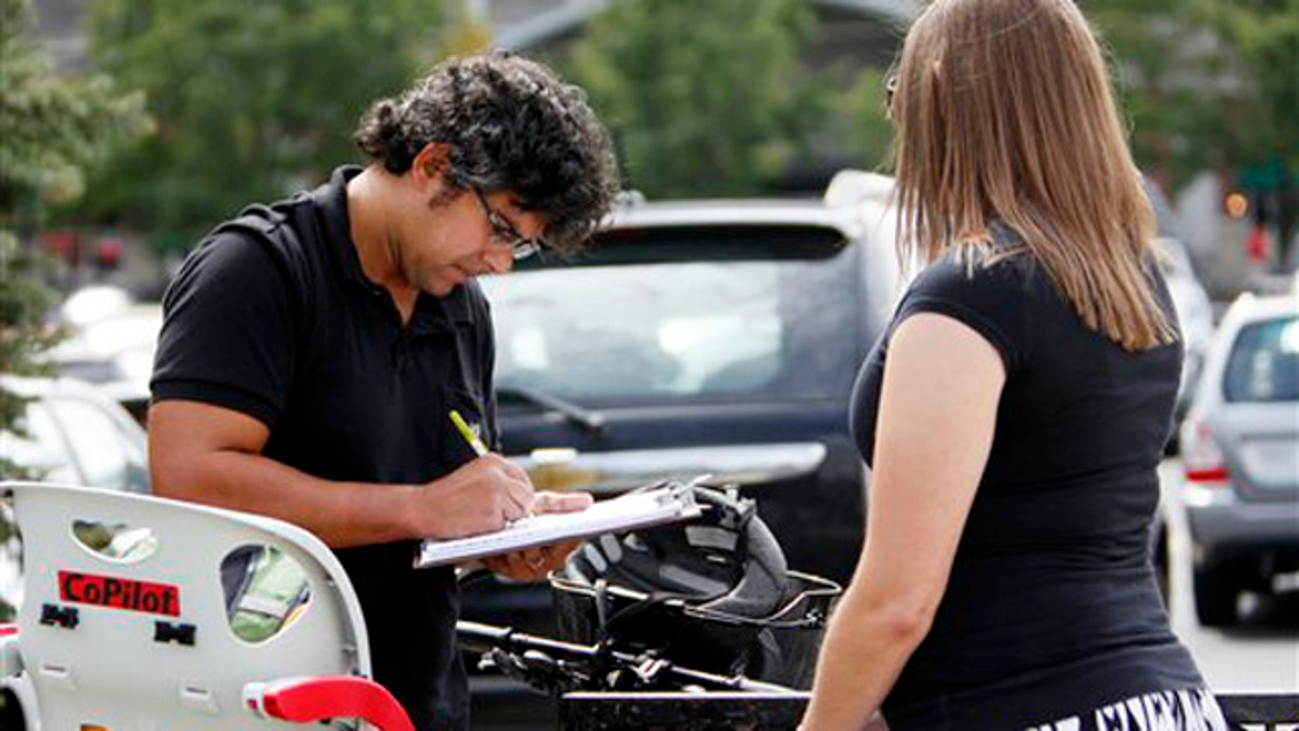 In this Sept. 9, 2011, photo, Mellissa Brown, right, a volunteer for Organizing for America, collects a signature from Jay Gupta for a petition in Columbus, Ohio, in a ballot repeal effort by opponents of the Ohio's new elections law.