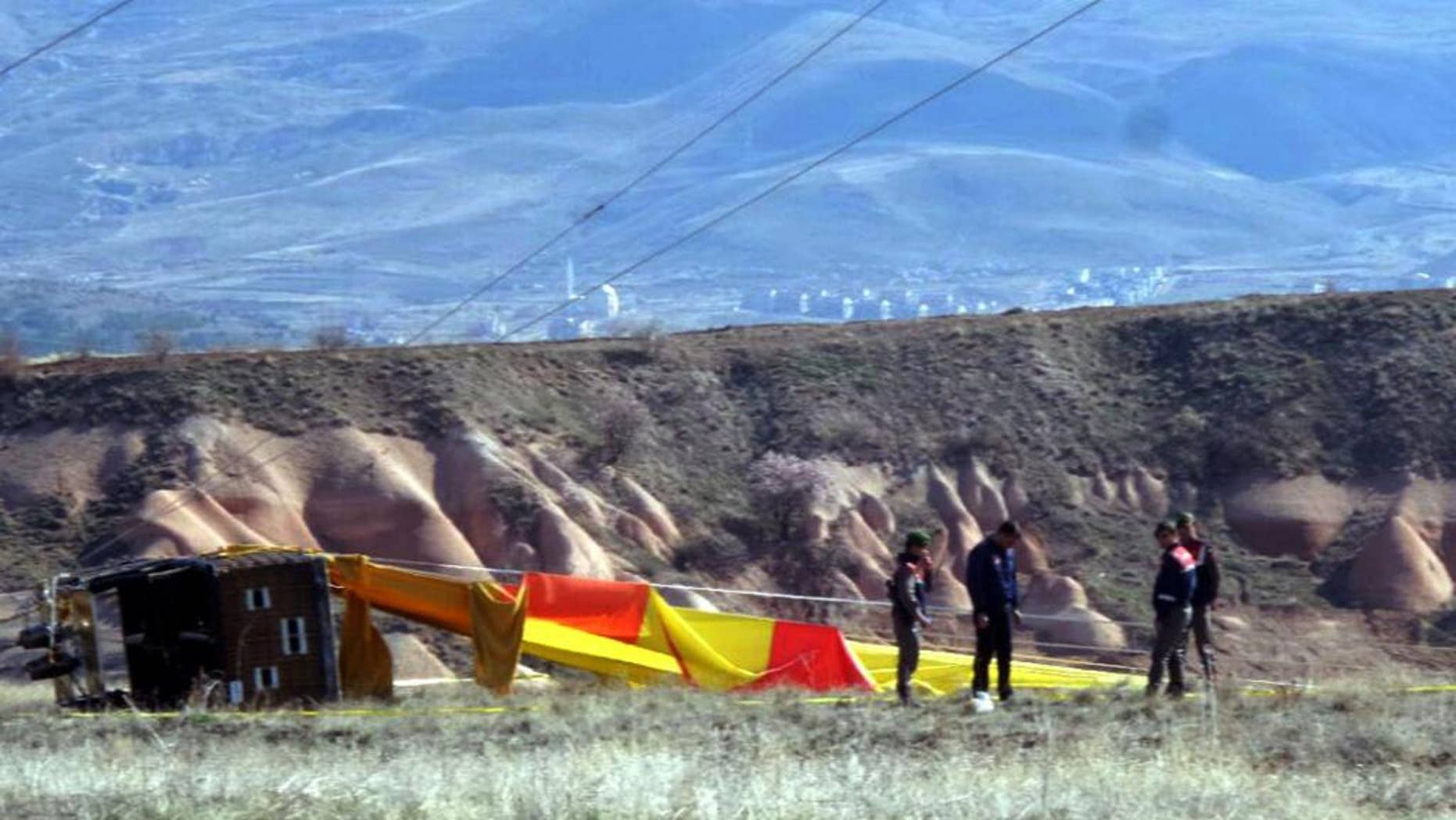 Security members investigate at the site after a hot air balloon hit a high-voltage transmission line and crashed near Cappadocia, a popular tourist destination in central Turkey, Sunday, April 9, 2017.