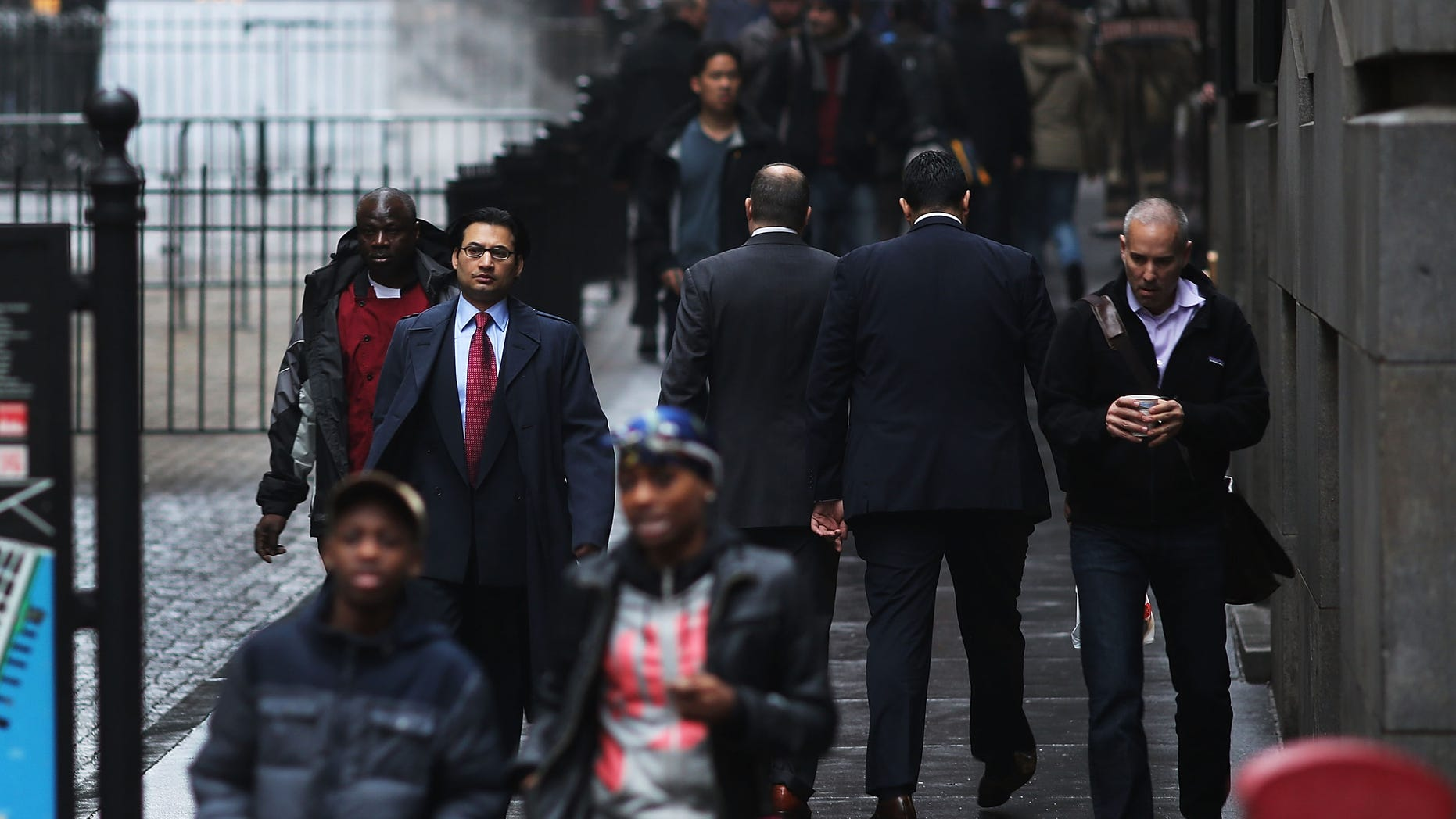 NEW YORK, NY - DECEMBER 10: People walk down Wall Street on December 10, 2012 in New York City. Stocks were little changed Monday morning as investors remained concerned over developments in Europe and ongoing fiscal cliff negotiations in Washington. The Dow Jones industrial average was up 24 points after the opening bell.  (Photo by Spencer Platt/Getty Images)
