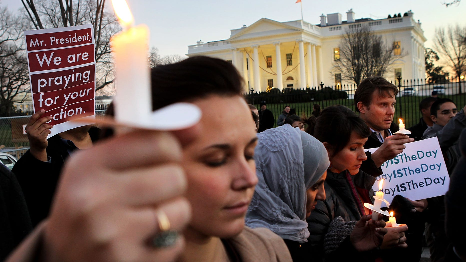 WASHINGTON, DC - DECEMBER 14:  People gather outside the White House to participate in a candle light vigil to remember the victims at the Sandy Hook Elementary School shooting in Newtown, Connecticut on December 14, 2012 in Washington, DC.  According to reports, there are about 27 dead, 18 children, after a gunman opened fire in at the Sandy Hook Elementary School. The shooter was also killed.  (Photo by Alex Wong/Getty Images)