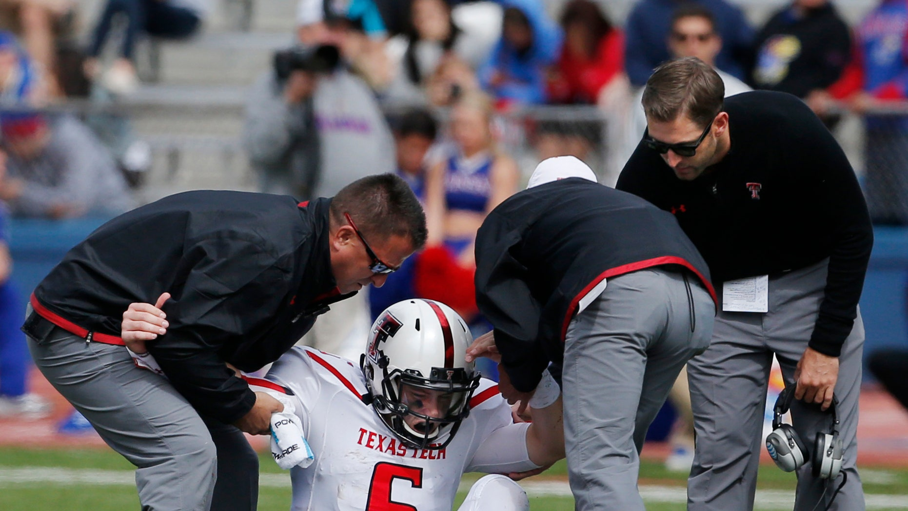 Texas Tech quarterback Baker Mayfield (6) is helped from the field by trainers and coach Kliff Kingsbury, right, during the second half of an NCAA college football game against Kansas in Lawrence, Kan., Saturday, Oct. 5, 2013. (AP Photo/Orlin Wagner)
