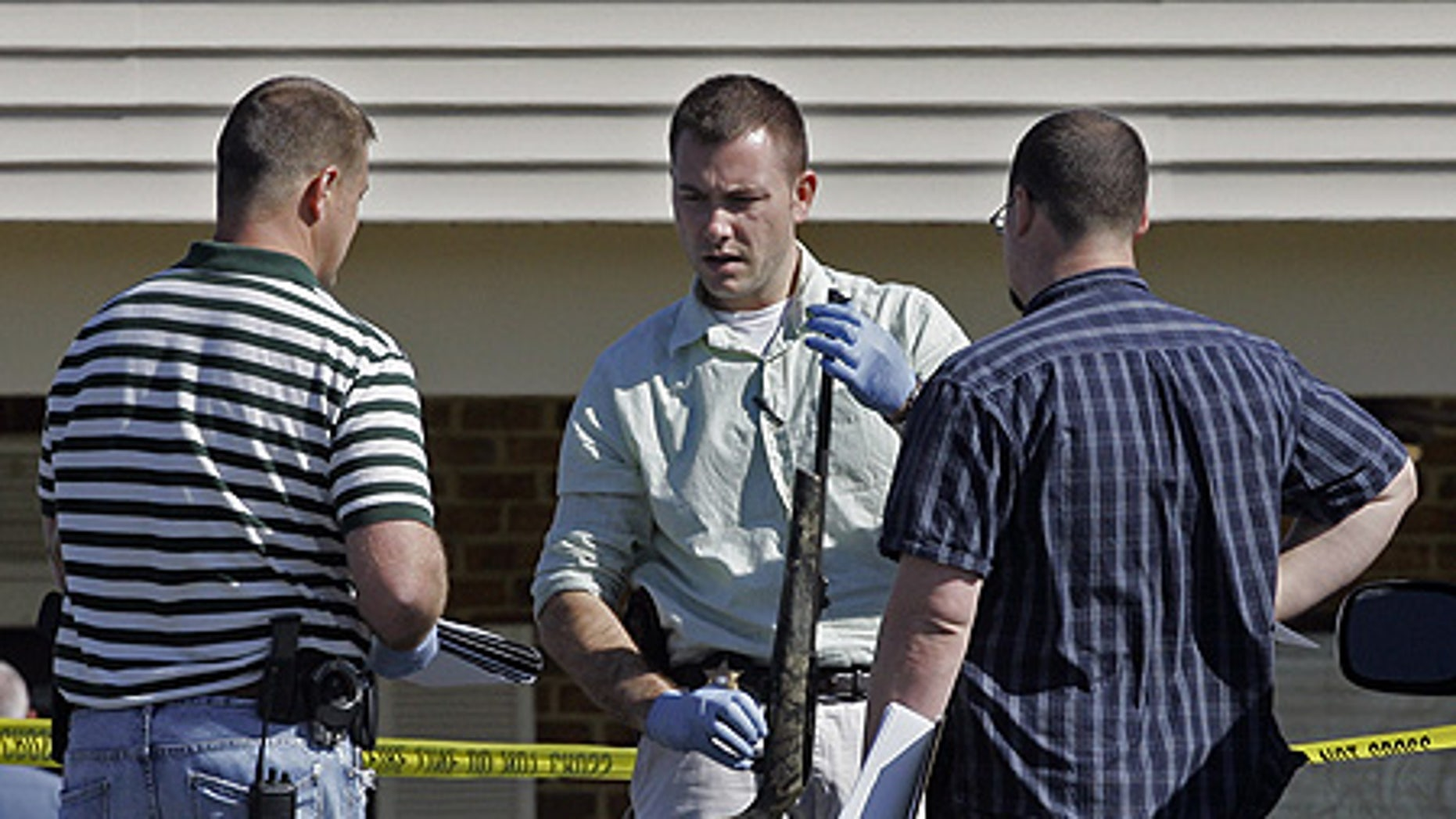 Mar. 29: Investigators examine a weapon at the scene where a gunman opened fire at a nursing home.