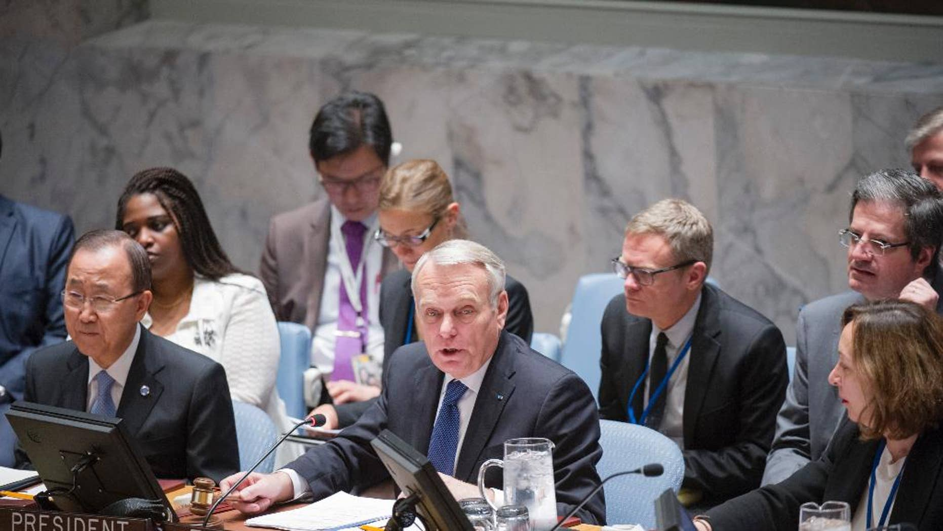 """In this photo provided by the United Nations, Jean-Marc Ayrault, center, Minister for Foreign Affairs and International Development of France, addresses the United Nations Security Council, Friday, June 10, 2016 at United Nations headquarters. U.N. Secretary-General Ban Ki-moon is seated to his left and Hasmik Egian, Acting Director of the Security Council Affairs Division, is to the right. Ayrault addressed a small group of reporters on Friday, warning that Israel's ban on Palestinians entering its territory following the """"abominable"""" attack on a popular cafe in Tel Aviv could escalate violence instead of focus attention on the need to pursue peace. (Rick Bajornas/The United Nations via AP)"""