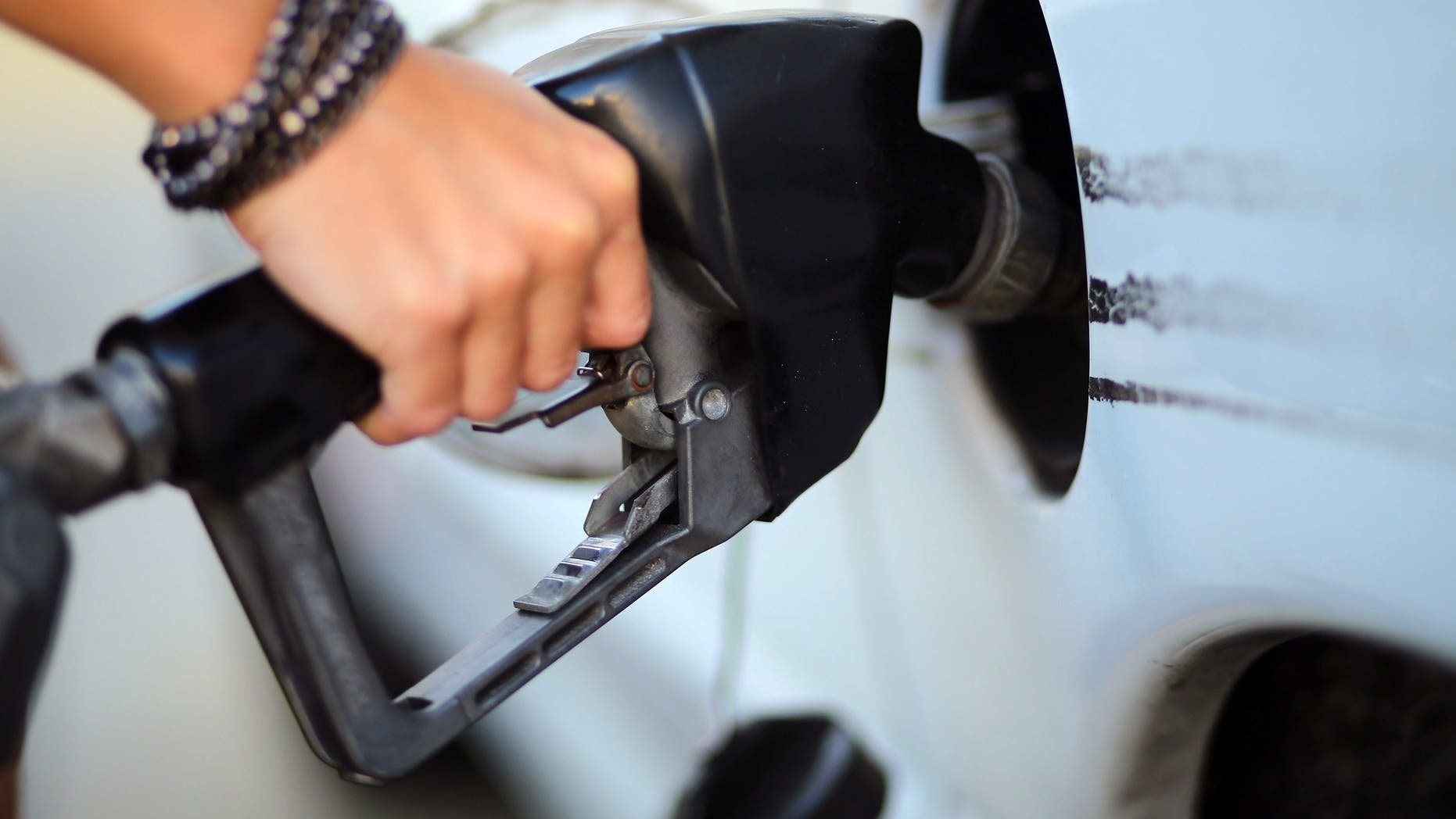A driver pumps gas in Miami, in Feb. 2013. Prices at the pump reached their lowest level in two years in December at $2.37 and have continued to fall, according to FOX Business. (Getty Images)