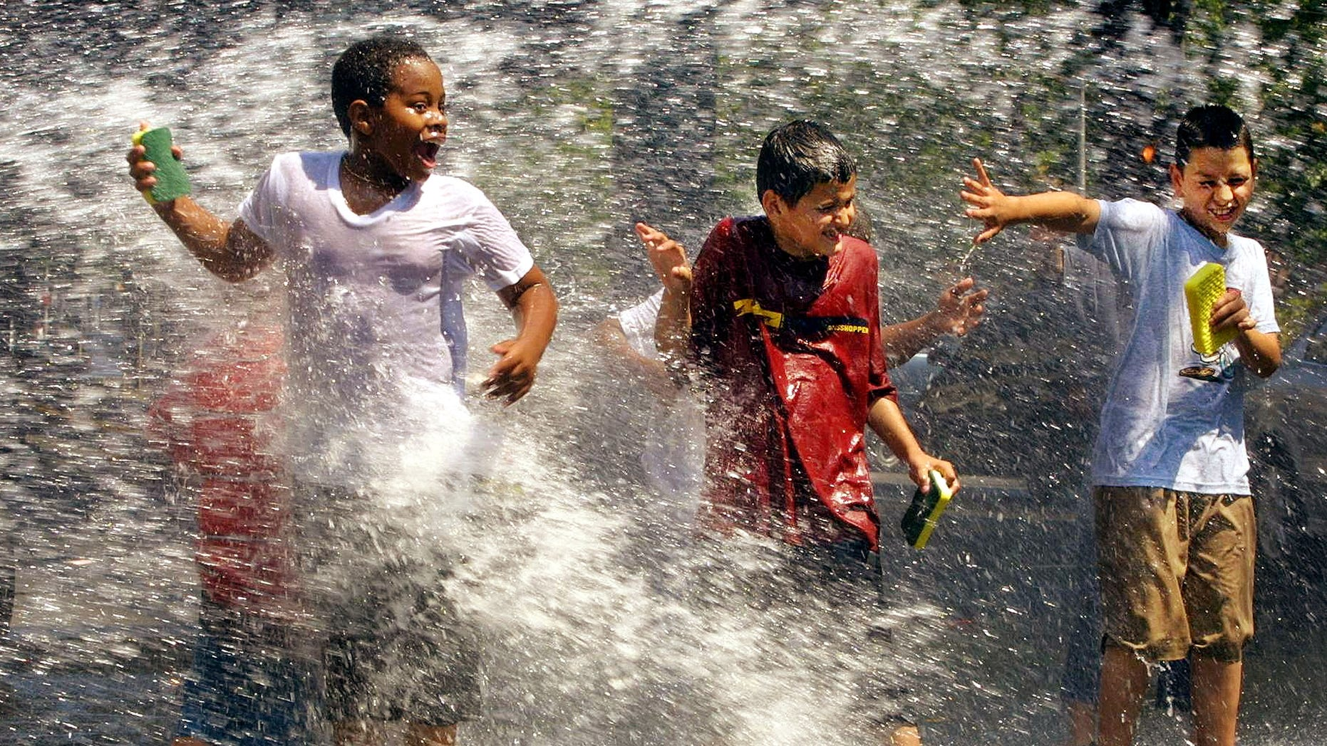 Children use a fire hydrant to cool off while washing cars in Washington Heights, New York City.