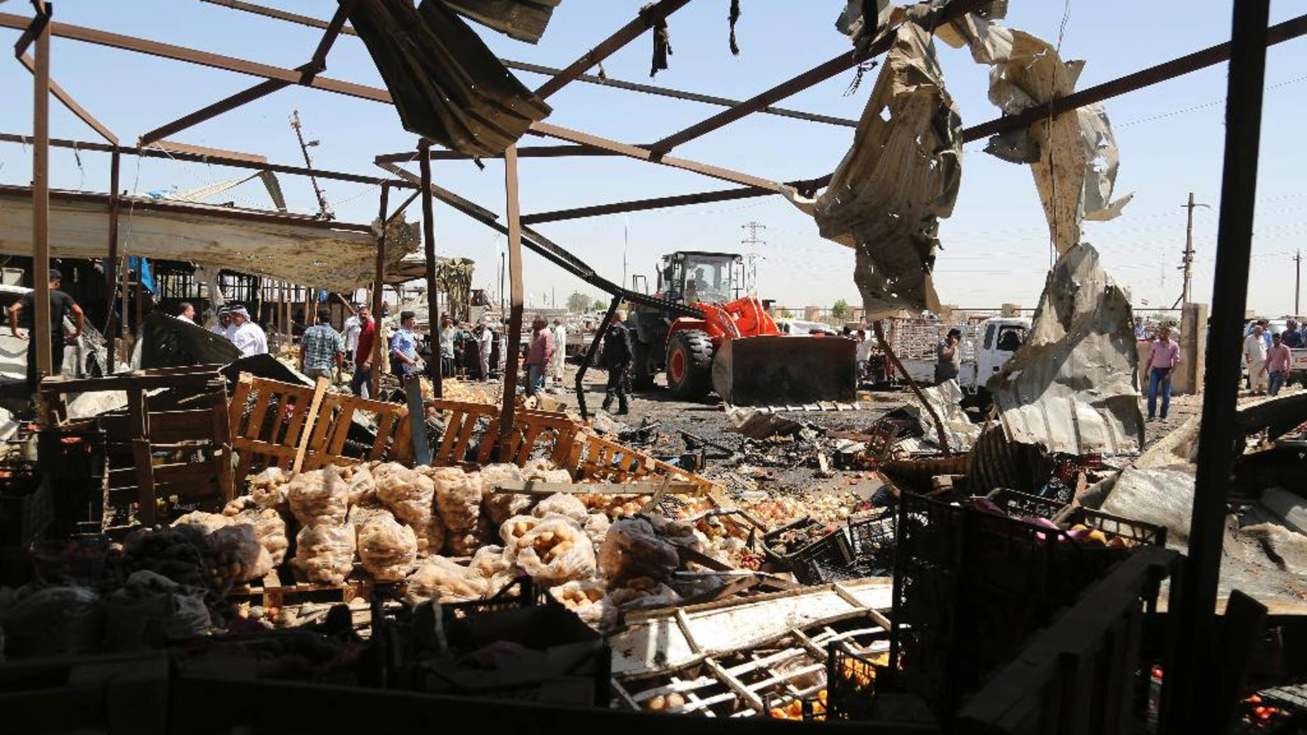 A bulldozer clears rubble at the scene of a deadly suicide car bombing at an outdoor vegetable and fruit market in a Shiite-dominated district in northeastern Baghdad, Iraq, Tuesday, July 12, 2016. The bomb on Tuesday, killed at least 10 people and injured tens of others, officials said. The developments came on the heels of two large-scale attacks claimed by the Islamic State group that killed more than 300 people last week. (AP Photo/Karim Kadim)