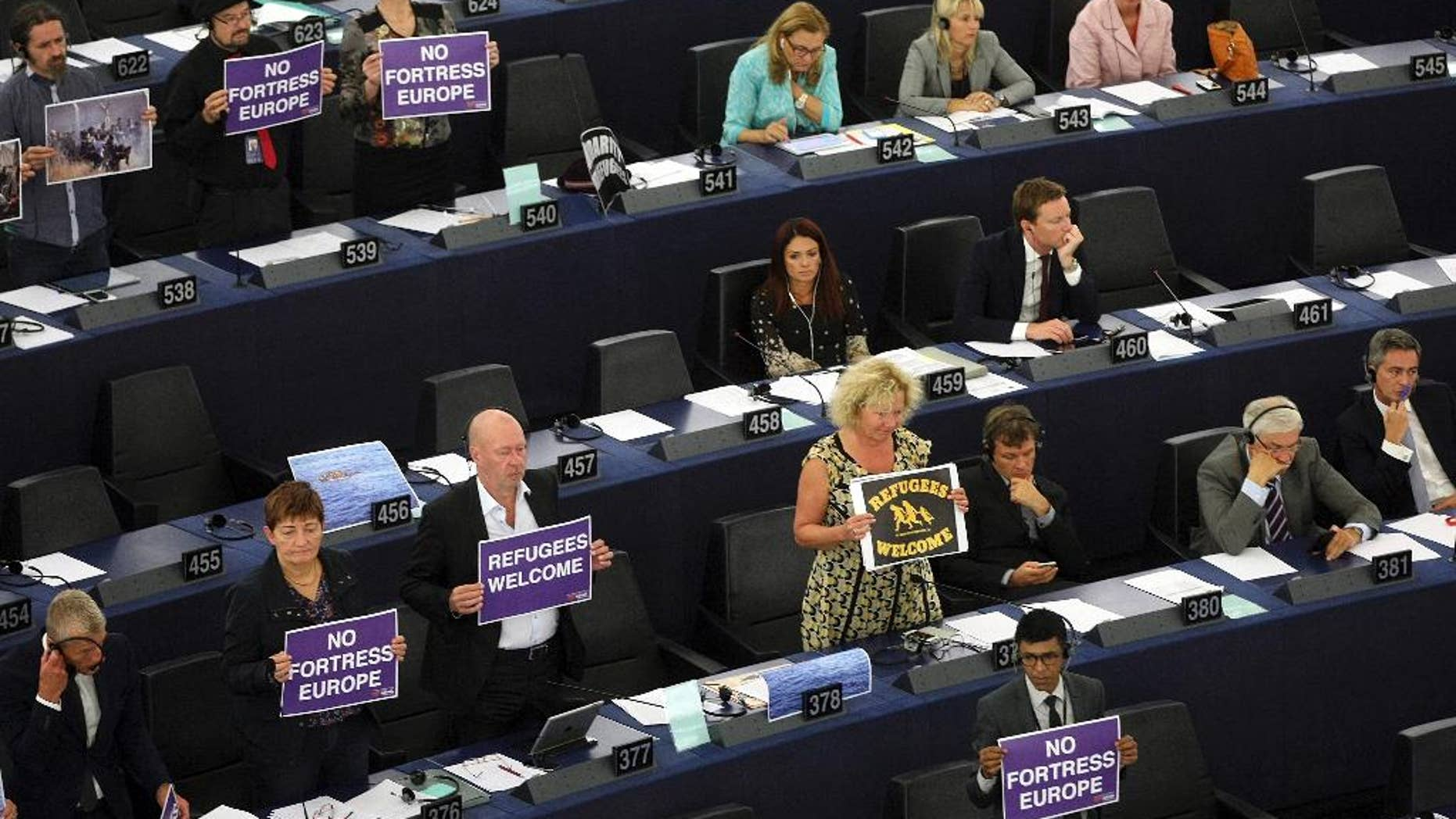 Parliament members holds posters while European Commission President Jean-Claude Juncker delivers his State of the Union address at the European Parliament in Strasbourg, eastern France, Wednesday, Sept.9, 2015. Juncker called on EU countries to agree by next week to share 160,000 refugees, warning that Greece, Italy and Hungary can no longer cope alone. (AP Photo/Christian Lutz)