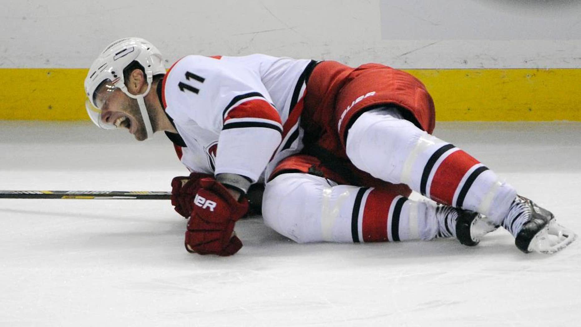 Carolina Hurricanes center Jordan Staal grimaces as he lays on the ice during the third period action of an NHL hockey preseason game against the Buffalo Sabres, Tuesday, Sept. 23, 2014, in Buffalo, N.Y. (AP Photo/Gary Wiepert)