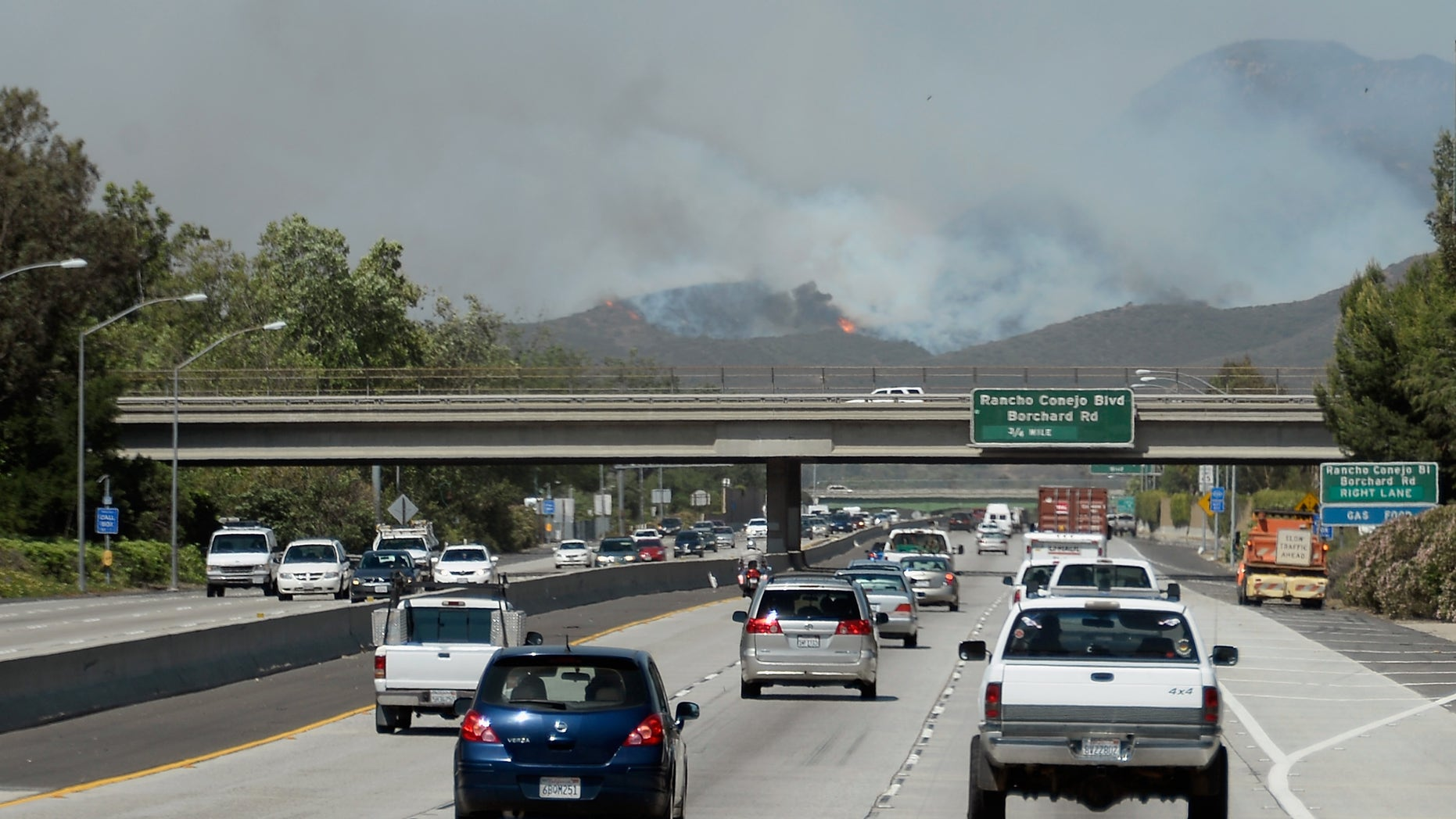 NEWBURY PARK, CA - MAY 02: Cars travel on the 101 Freeway as a wildfire burns in the hills nearby on May 2, 2013 in Newbury Park, California. Winds have made fighting the blaze, called the Springs Fire, more difficult and authorities have ordered some mandatory evacuations in the area. (Photo by Kevork Djansezian/Getty Images)