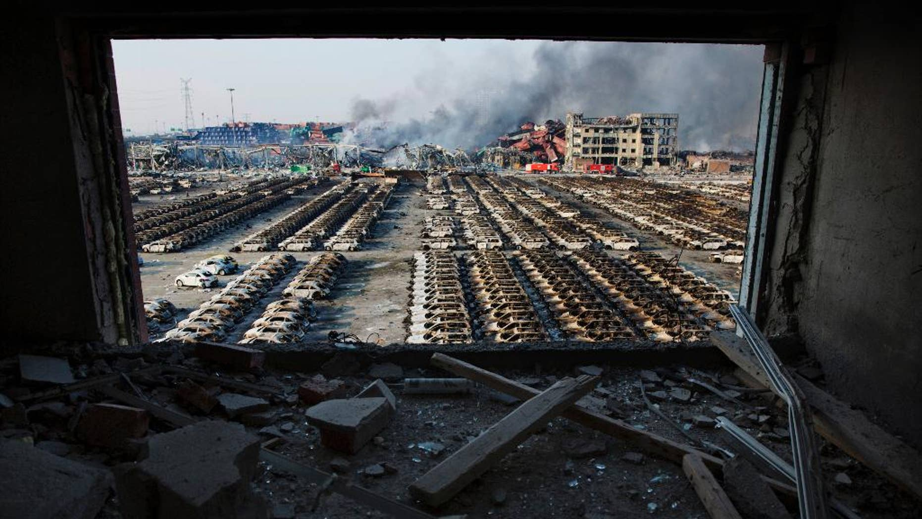 FILE - In this Aug. 13, 2015 photo, a shattered window frames the site of an explosion at a port warehouse in northeastern China's Tianjin municipality. Chinese prosecutors have detained 11 government officials and company executives over a massive warehouse explosion that killed at least 139 people in the country's worst industrial disaster in recent years.  (AP Photo/Ng Han Guan. File)