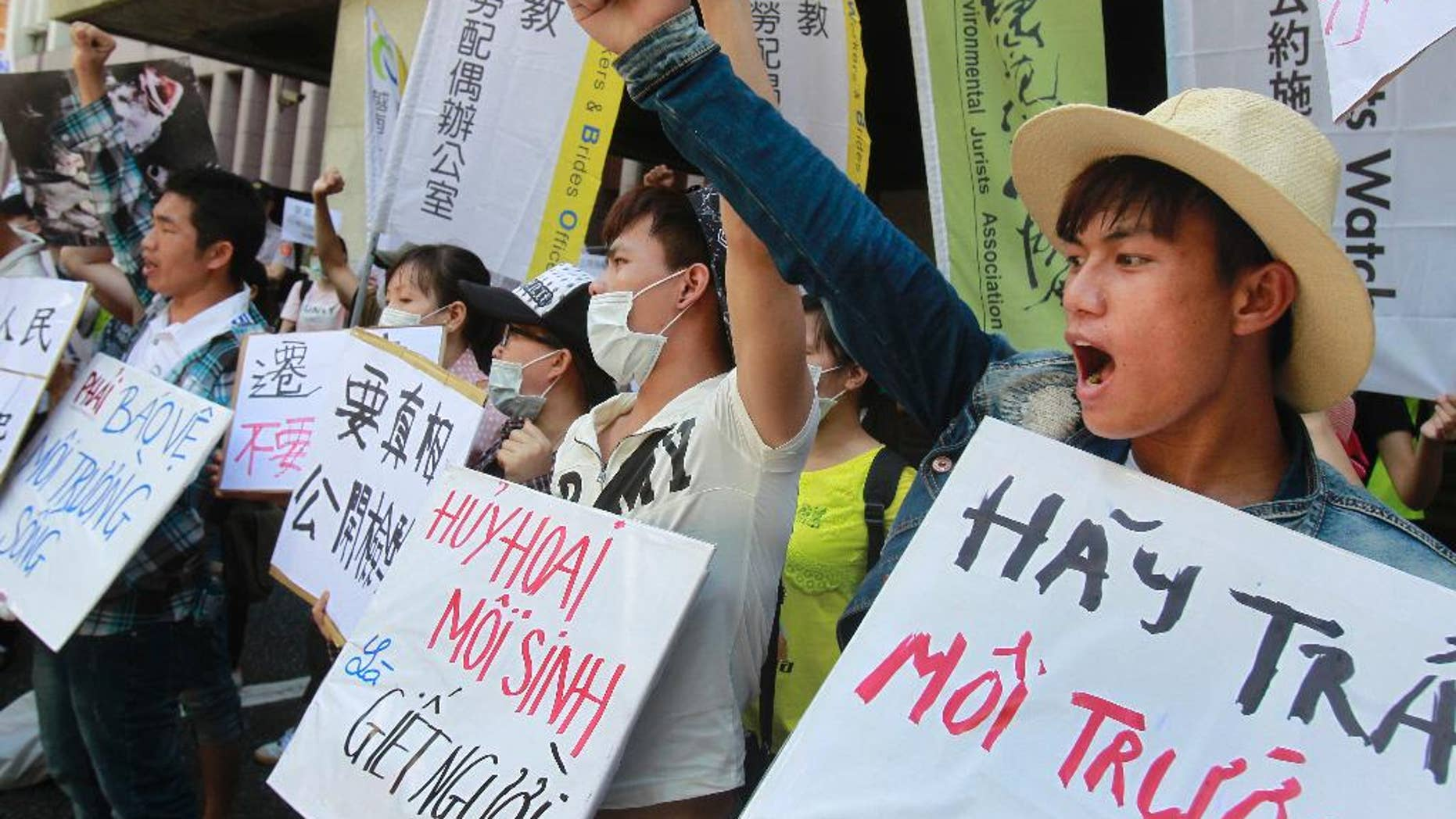 "FILE - In this Aug. 10, 2016 file photo, Vietnamese activists shout slogans and hold placards reading ''Destroying the environment is killing, ""left, and ''Return clean seawater to us'' during a protest to urge Formosa Plastics Group to take responsibilities for the cleanup in Vietnam, in Taipei, Taiwan.    Hundreds of Vietnamese fishermen have filed claims seeking compensation from a Taiwanese steel company that acknowledged its toxic chemicals caused a massive fish kill, a local priest helping the fishermen said Tuesday, Sept. 27, 2016.  (AP Photo/Chiang Ying-ying, File)"