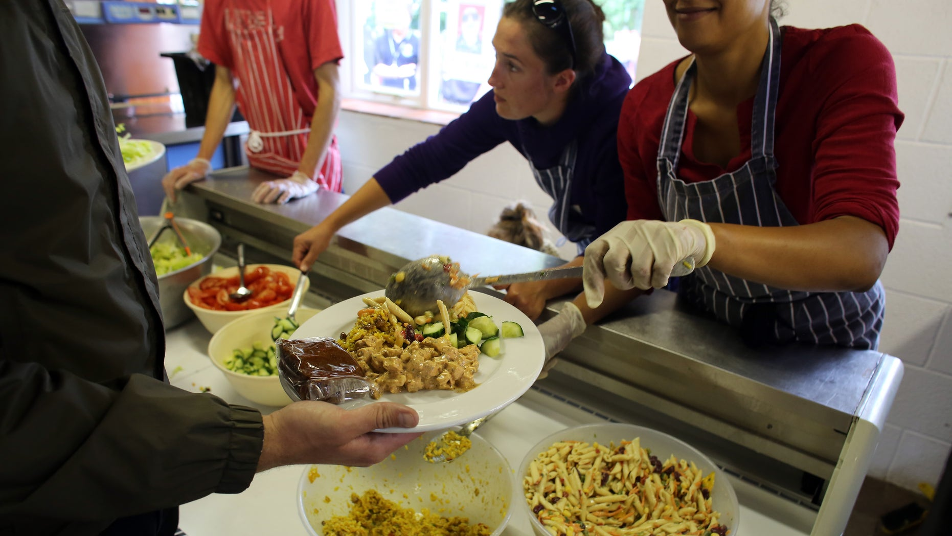 GLASTONBURY, ENGLAND - JUNE 20:  Festival caterers serve lunch at Goose Hall, the on-site staff canteen, at the Glastonbury Festival of Contemporary Performing Arts site at Worthy Farm, in Pilton on June 20, 2013 in Glastonbury, England.  In a weeks time, the diary farm in Somerset will be playing host to one of the largest music festivals in the world and this year features headline acts Artic Monkeys, Mumford and Sons and the Rolling Stones. Tickets to the event which is now in its 43rd year sold out in minutes and that was before any of the headline acts had been confirmed. The festival, which started in 1970 when several hundred hippies paid 1 GBP to watch Marc Bolan, now attracts more than 175,000 people over five days.  (Photo by Matt Cardy/Getty Images)