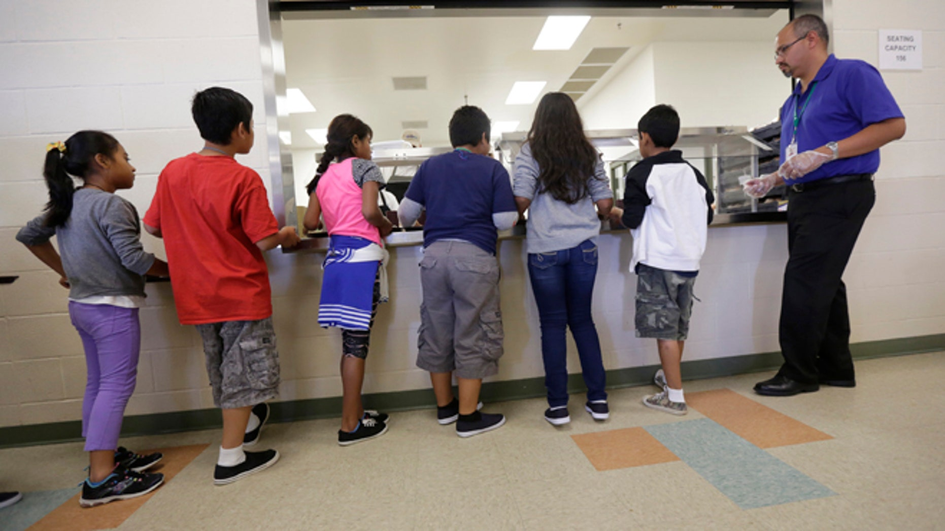 Detained immigrant children line up in the cafeteria at the Karnes County Residential Center, in Karnes City, Texas.